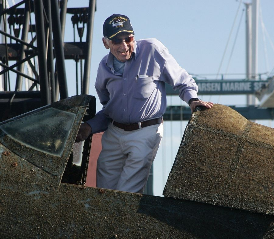Chuck Greenhill of Mettawa is all smiles as he stands in the cockpit of a World War II F4U-1 Corsair fighter plane that was recovered from Lake Michigan Monday by A&T Recovery at Larsen Marine at Waukegan Harbor. Greenhill financed the recovery of the Corsair from Lake Michigan.