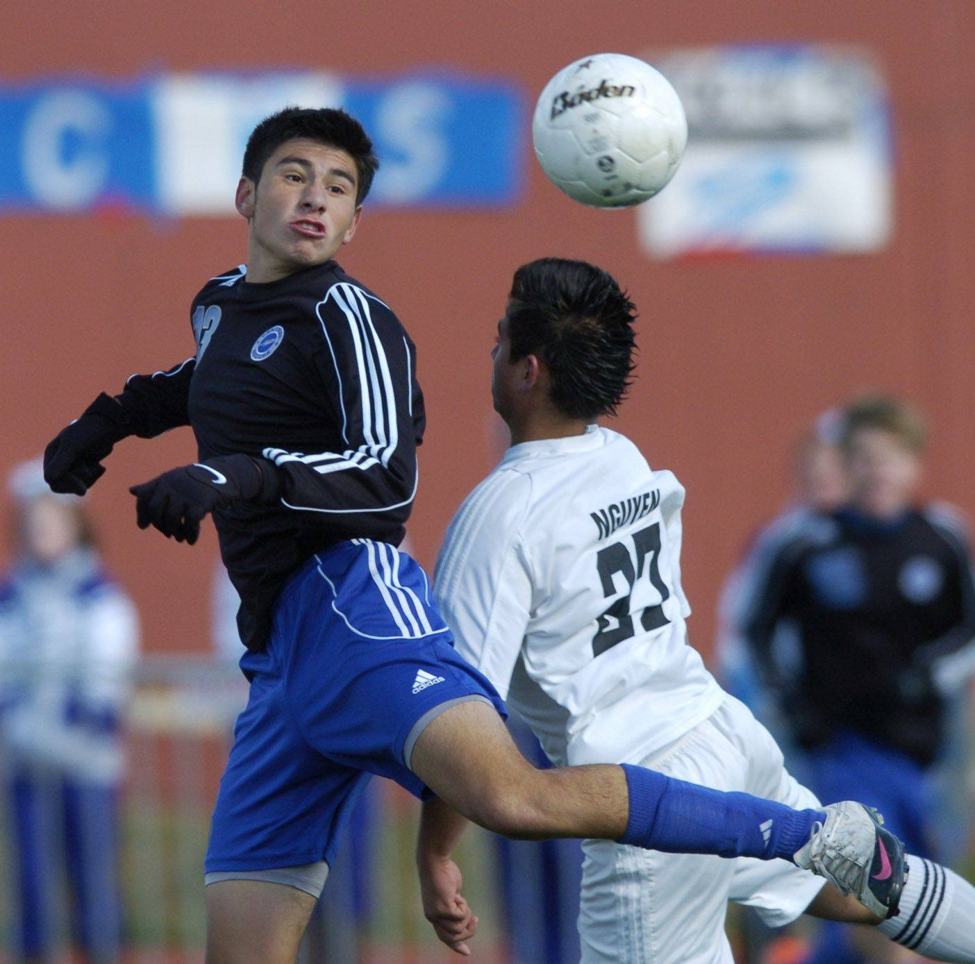 Burlington Central's Erick Uribe directs the ball with a header past Ridgewood's Maciej Nguyen during Friday's Class 2A state boys soccer semifinal.