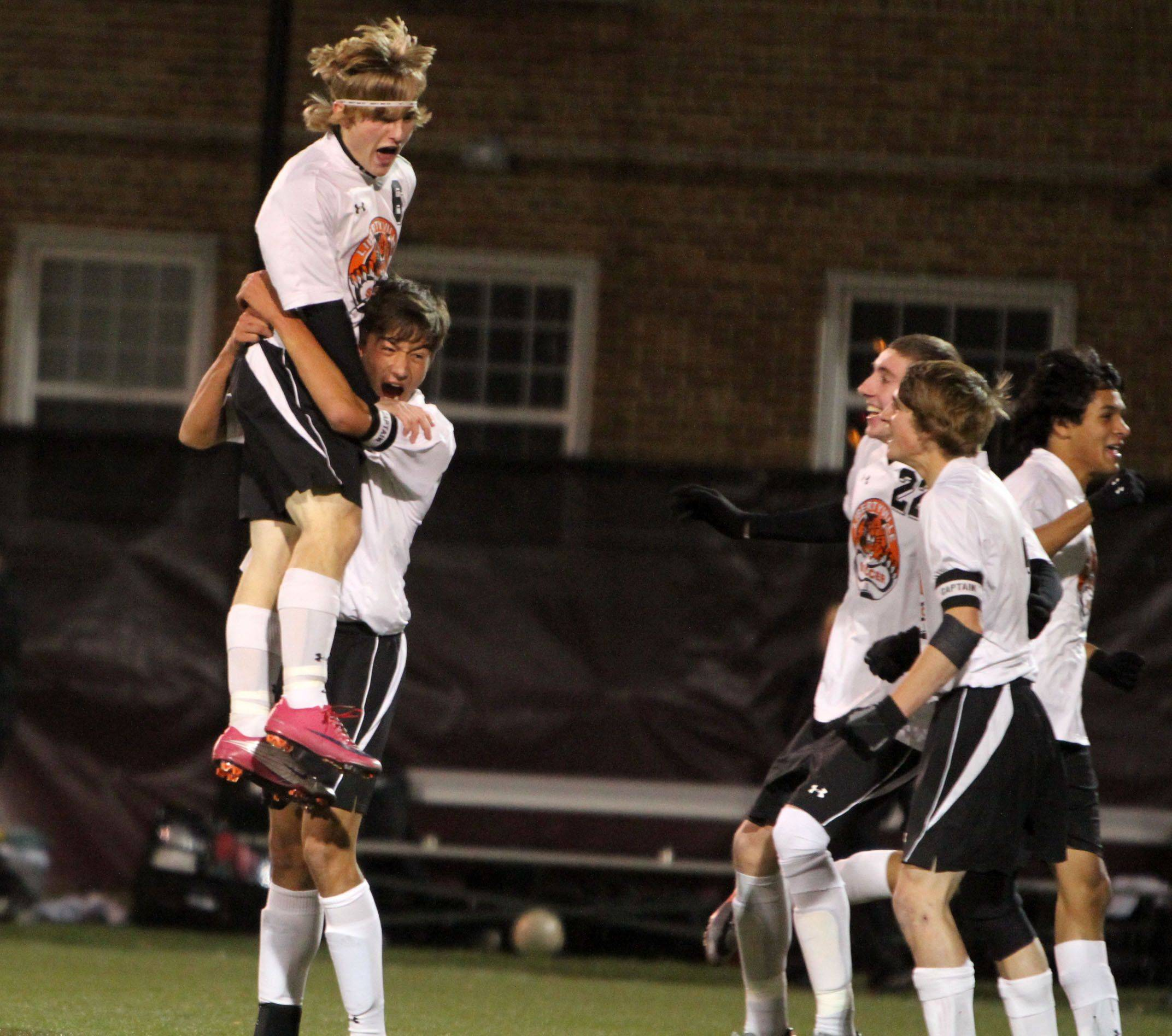 Libertyville's Landon Eyre lifts teammate Joey Ruppert to celebrate a goal during Tuesday's Class 3A super-sectional match at Loyola Soccer Park in Chicago against Maine West.