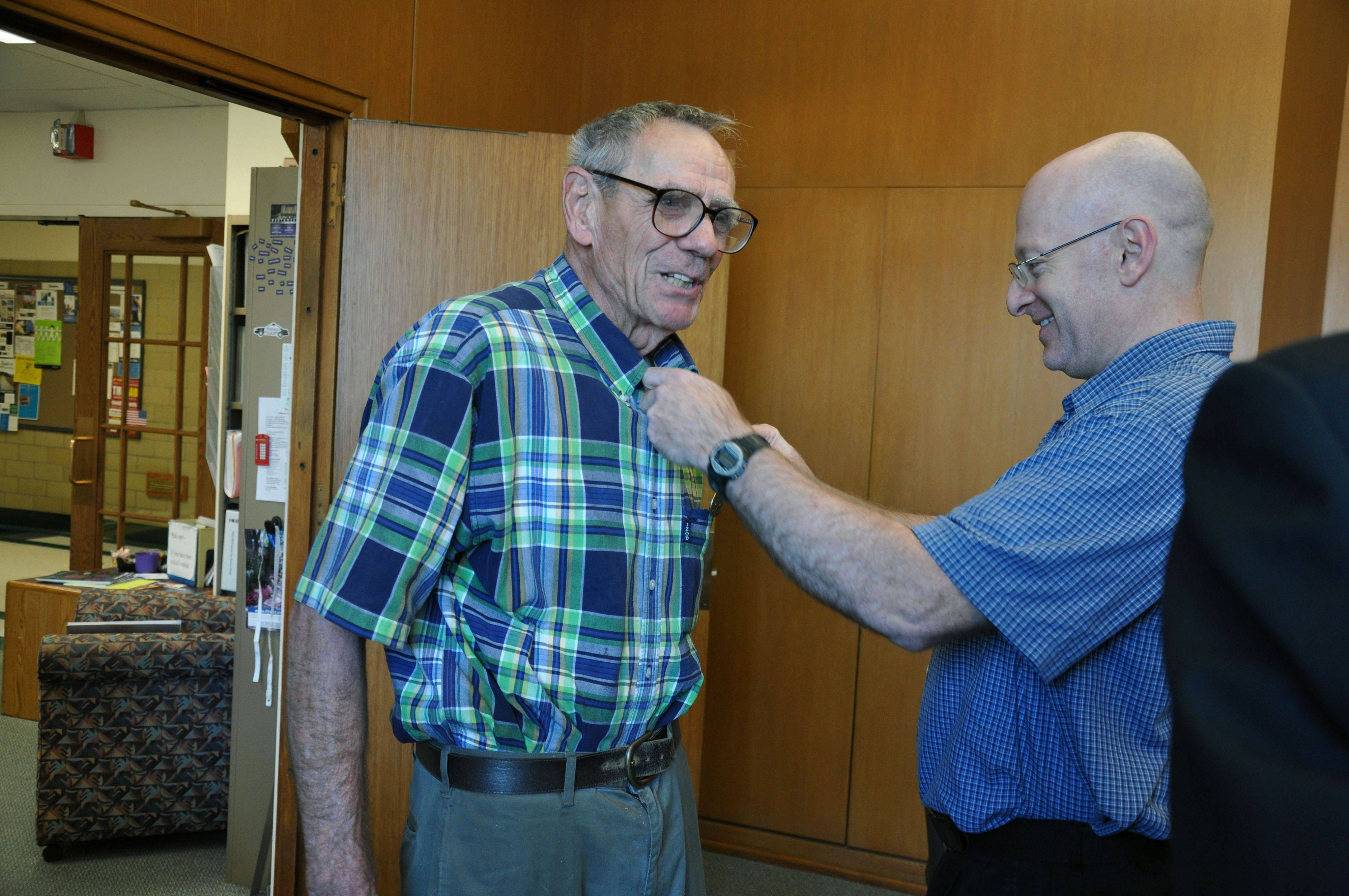 Co-worker Mark Seniw pins a medal to the chest of Arlington Heights resident Jim Hahn during a ceremony at Northwestern University on Tuesday. Hahn, a former Navy Seabee, never received the medal, despite earning it during World War II.