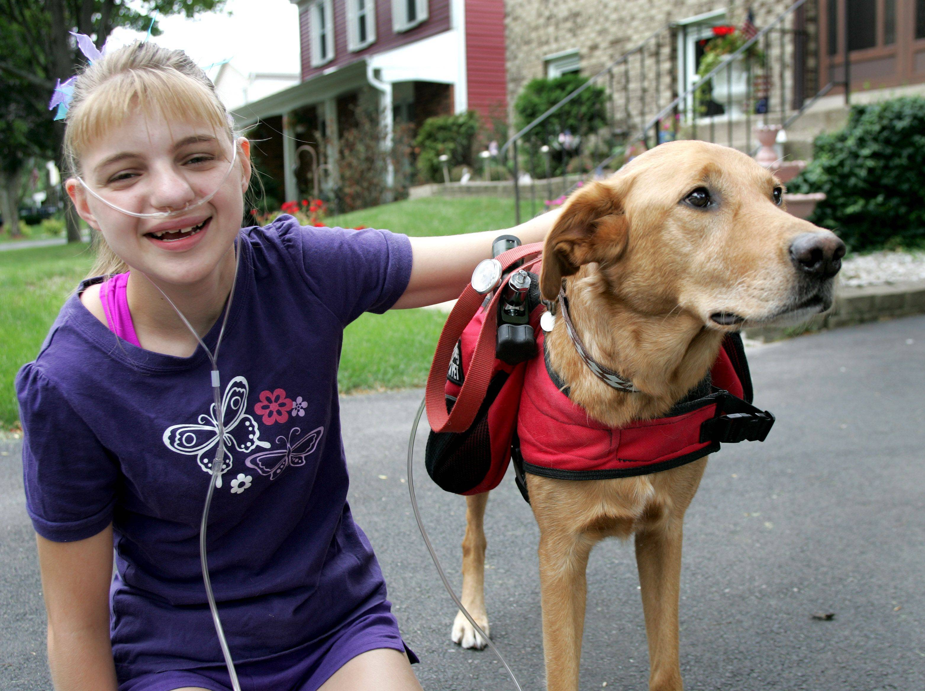 Jenny Youngwith's service dog, Simba, a 6-year-old yellow Lab mix, won't be allowed to carry her oxygen tanks on the basketball court.