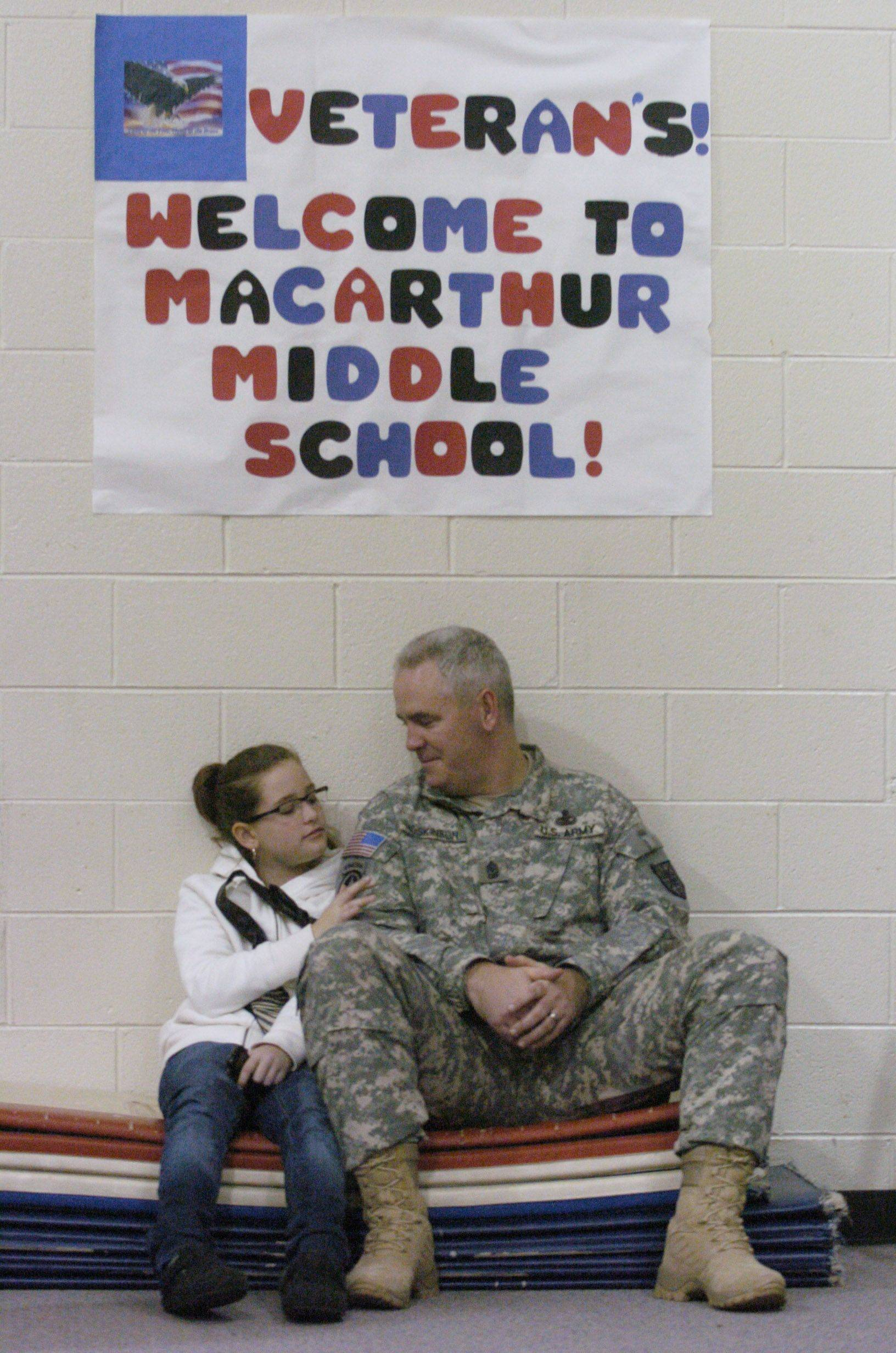 Payton Hoskinson, 9, of Chicago, sits with her dad, Tom, a Sergeant-Major in the U.S. Army Reserves, following a breakfast for Veterans at MacArthur Middle School, Prospect Heights, Thursday. Tom is a Mt. Prospect Police officer who has been deployed with the Army in Afghanistan.