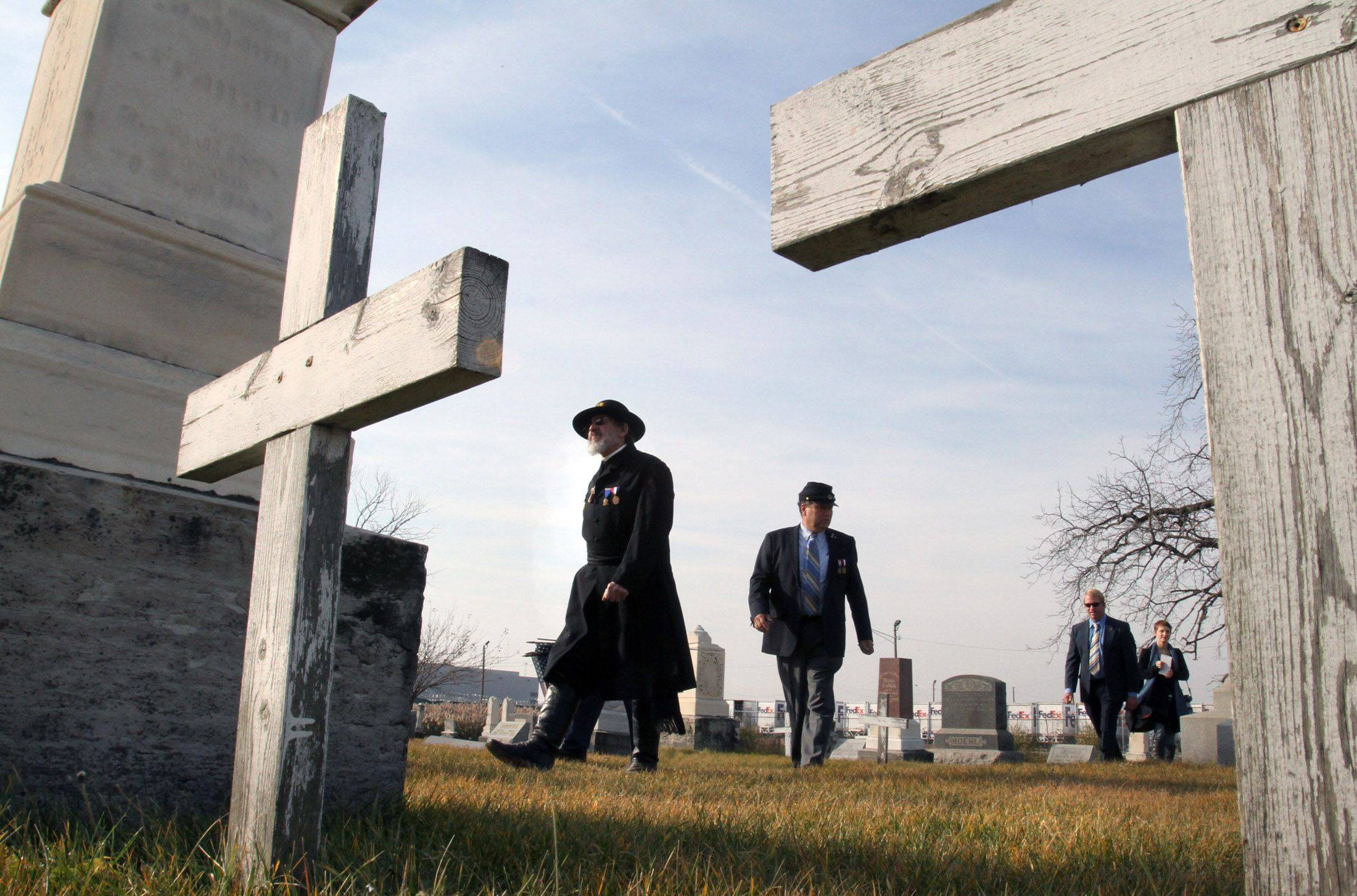 Jerry Kowalski, left, of Elmhurst, National Chaplain for the Sons of Union Veterans walks through Johannes Cemetery just after the memorial ceremony on Veterans Day at the cemetery just south of O'Hare International Airport in Chicago on Thursday, November 11.