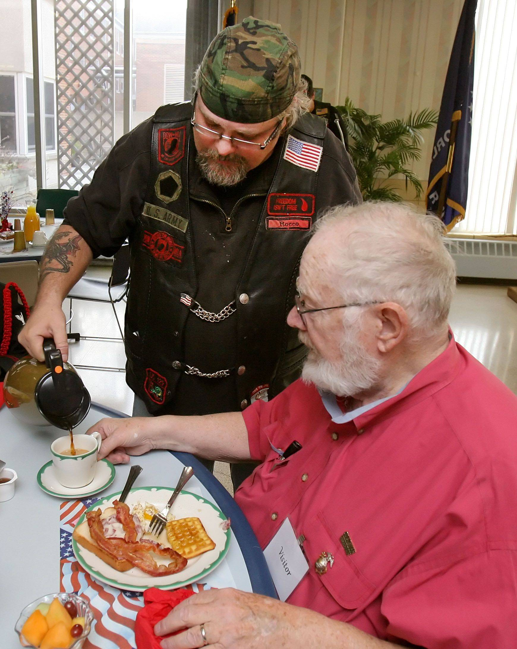 Rocco Jorgensen of the Second Brigade Motorcycle Club and a resident of Lake Villa, pours coffee for veteran Peter Phillips of Libertyville at the Winchester House in Libertyville Thursday. The Second Brigade Motorcycle Club sponsored a breakfast for veterans at Winchester House. Phillip's wife is a resident at Winchester House.