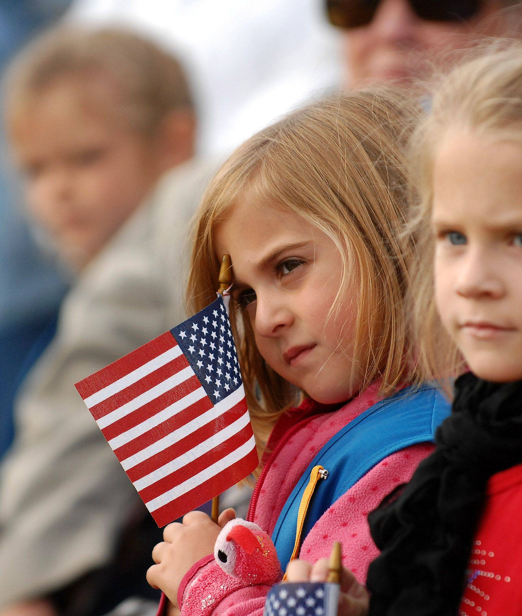 5-year-old Zoey Pozen of Elburn holds a flag as she watches the ceremony during the Elburn Veteran's Day ceremony Thursday.