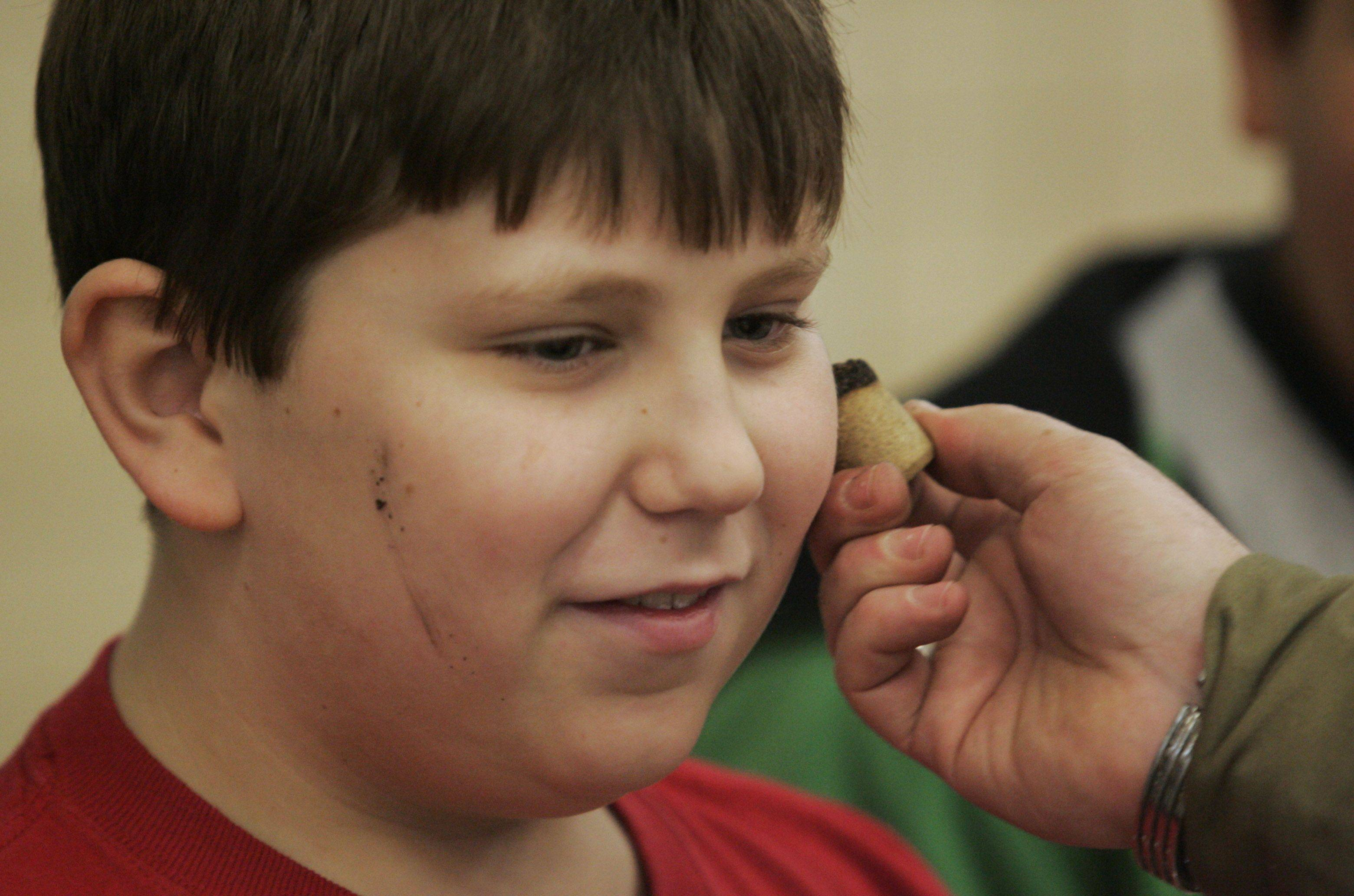 Hampshire Middle School sixth-grader Michael Saracco tries out some face camouflage from a burned wine cork during an interactive display on Veterans Day. Paratroopers used whatever they had on hand to help hide themselves on night drops during World War II.