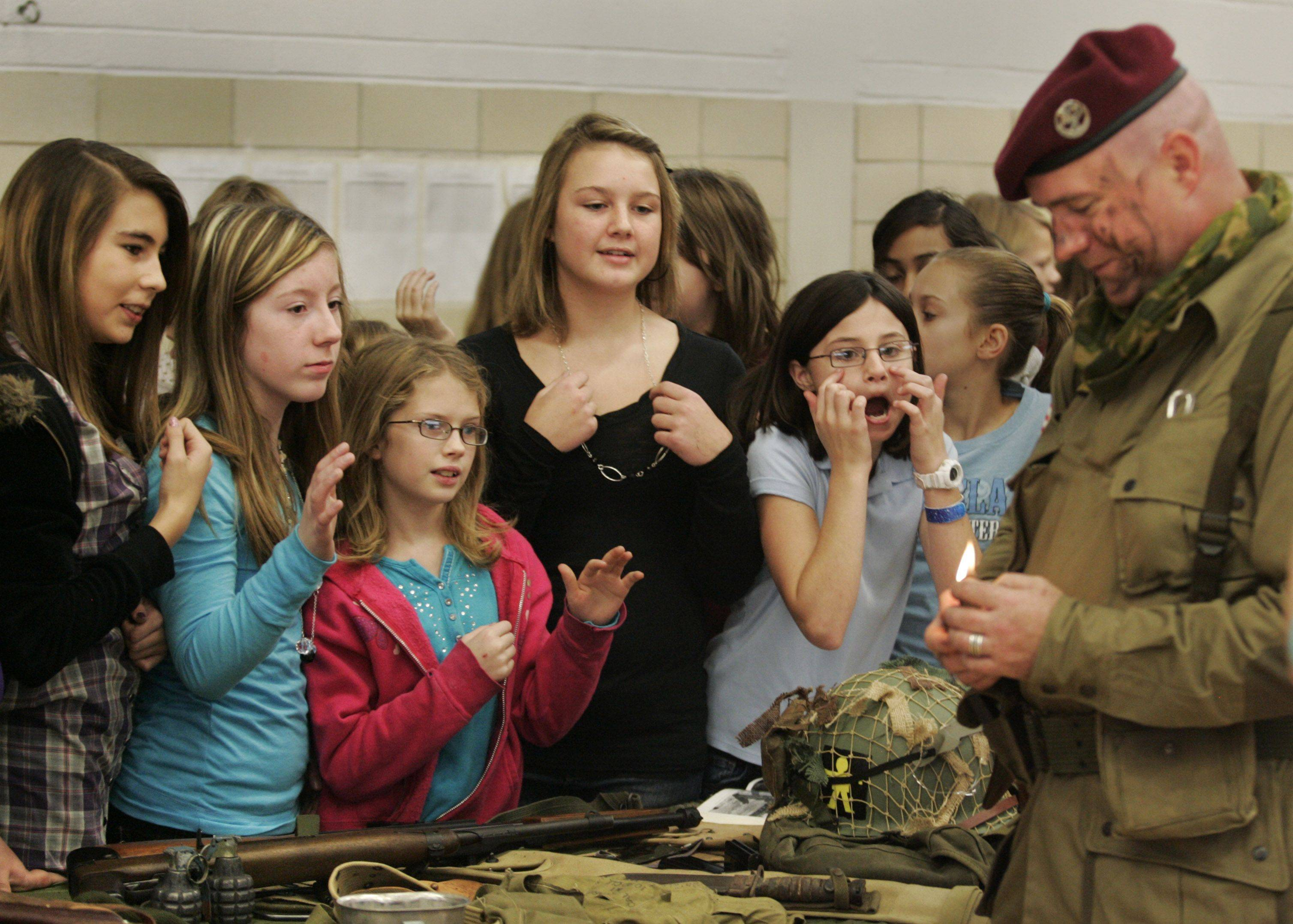 Sixth-grade girls wait anxiously for their chance to have burned wine cork rubbed on their faces during an interactive display on Veterans Day at Hampshire Middle School. Re-enactor Stephane Goupil demonstrated how troops would burn the ends of wine corks and them smear them on their faces to provide additional camouflage during night parachute drops. Goupil, who served as an infantryman in France, now lives in Barrington and is a member of the 509th parachute infantry battalion re-enactment group.