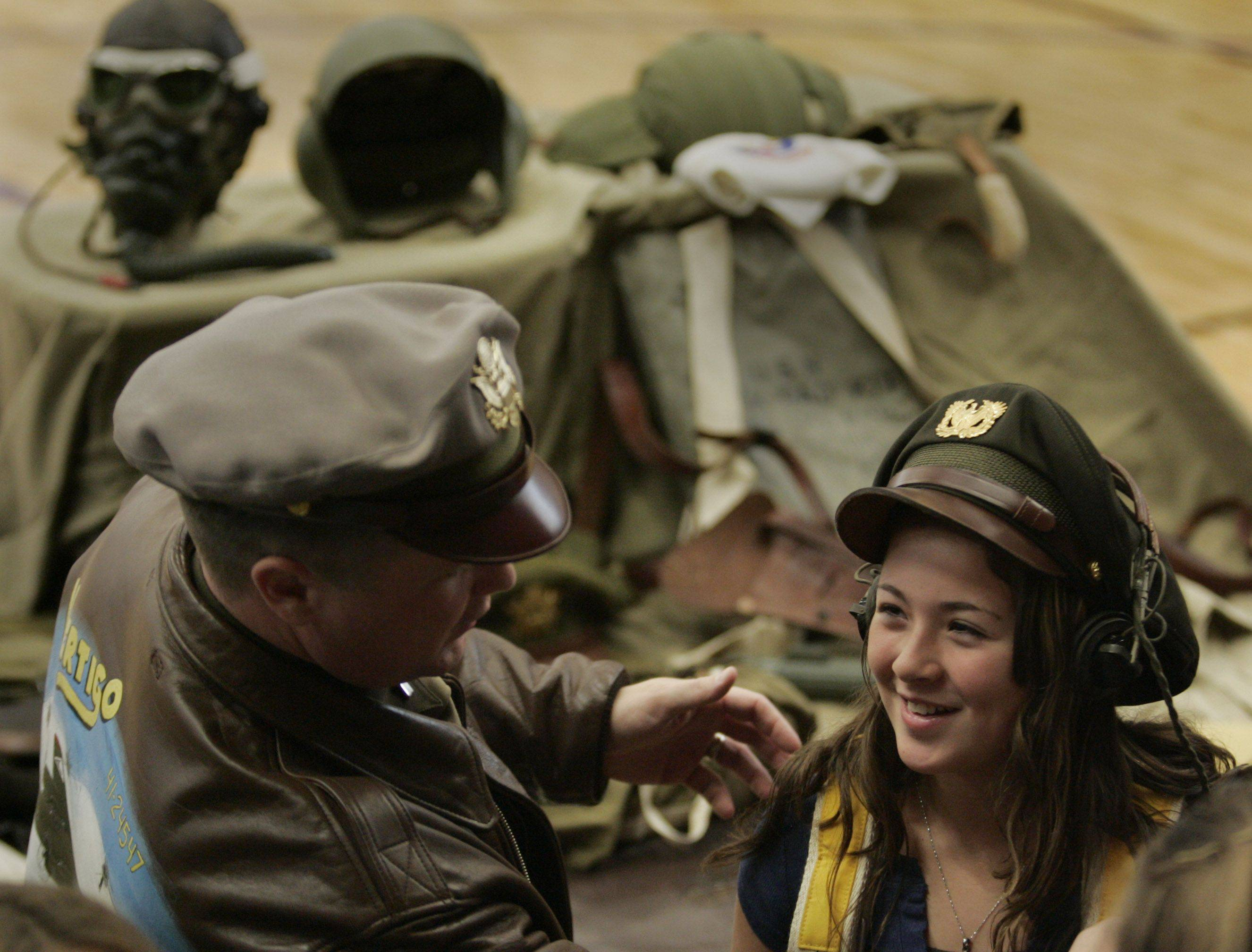 Sixth-grader McKenna Graham tries on gear worn by B-17 bomber pilots in World War II including a chest pack parachute, crusher cap and radio headphones during an interactive display on Veterans Day at Hampshire Middle School. The B-17 pilot at left, a member of the national Historical Re-enactment Society, asked not to be identified.