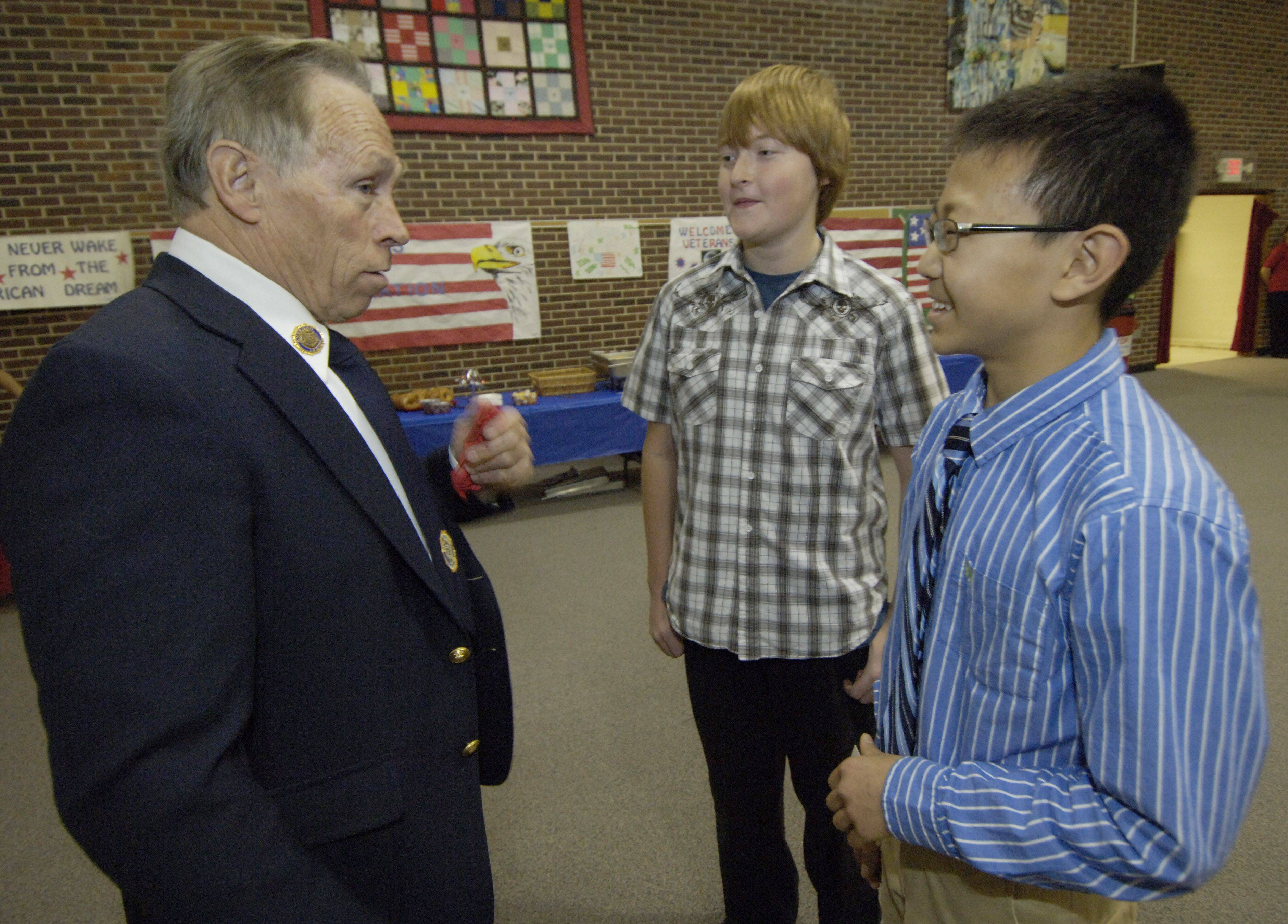 Dennis Kersting of Des Plaines, who served the Navy during the Vietnam War, talks with eighth graders Tyler Anderson, center, and Paul Kim during a breakfast for Veterans at MacArthur Middle School, Prospect Heights, Thursday.