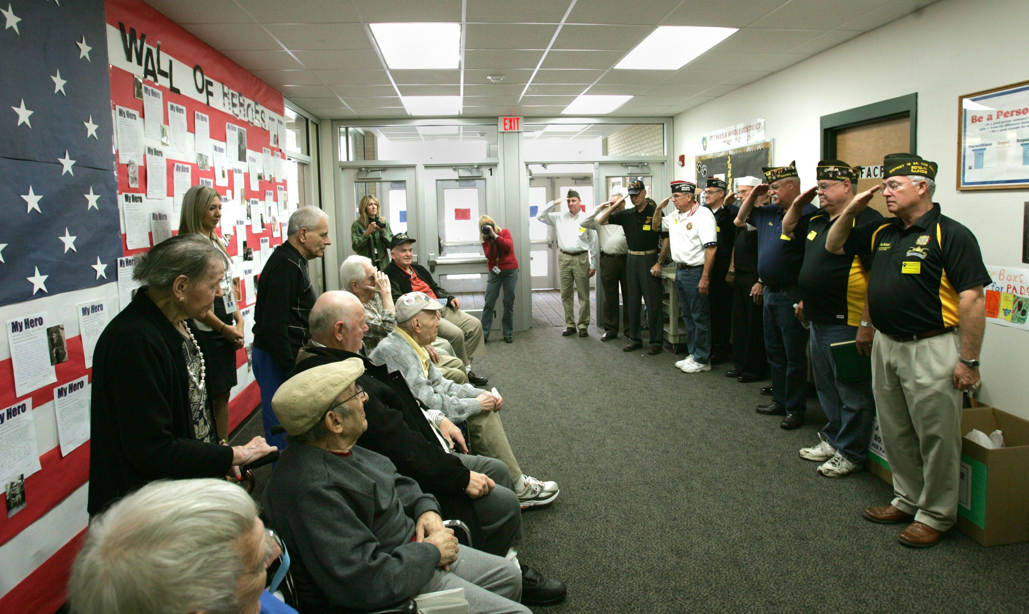 At right, VFW Bloomingdale Post 7539 members salute World War II veterans from the Lee Manor Retirement home in Des Plaines, at DuJardin Elementary School in Bloomingdale.