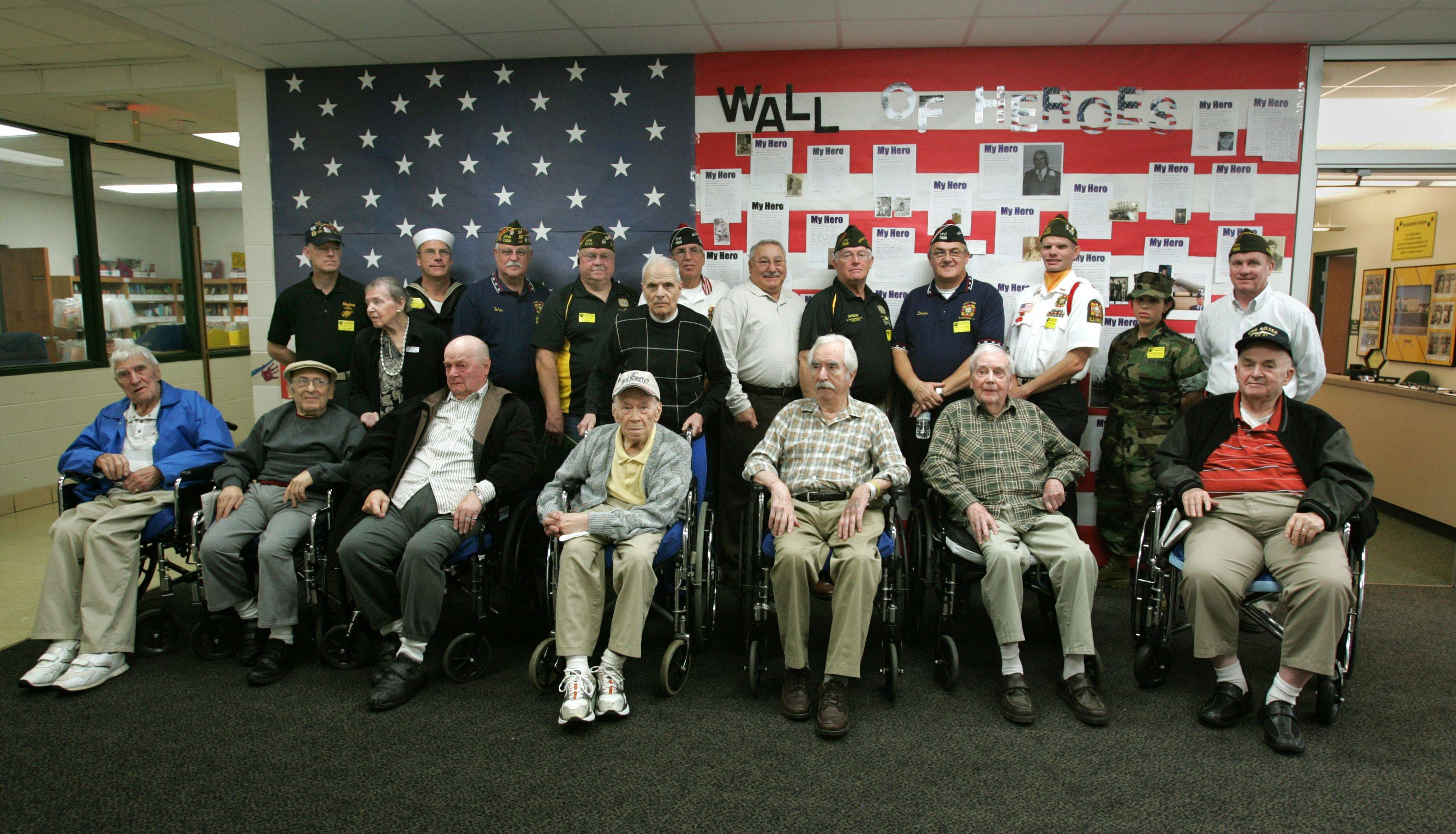 VFW Bloomingdale Post 7539 members stand behind World War II veterans from the Lee Manor Retirement home in Des Plaines, at DuJardin Elementary School in Bloomingdale.