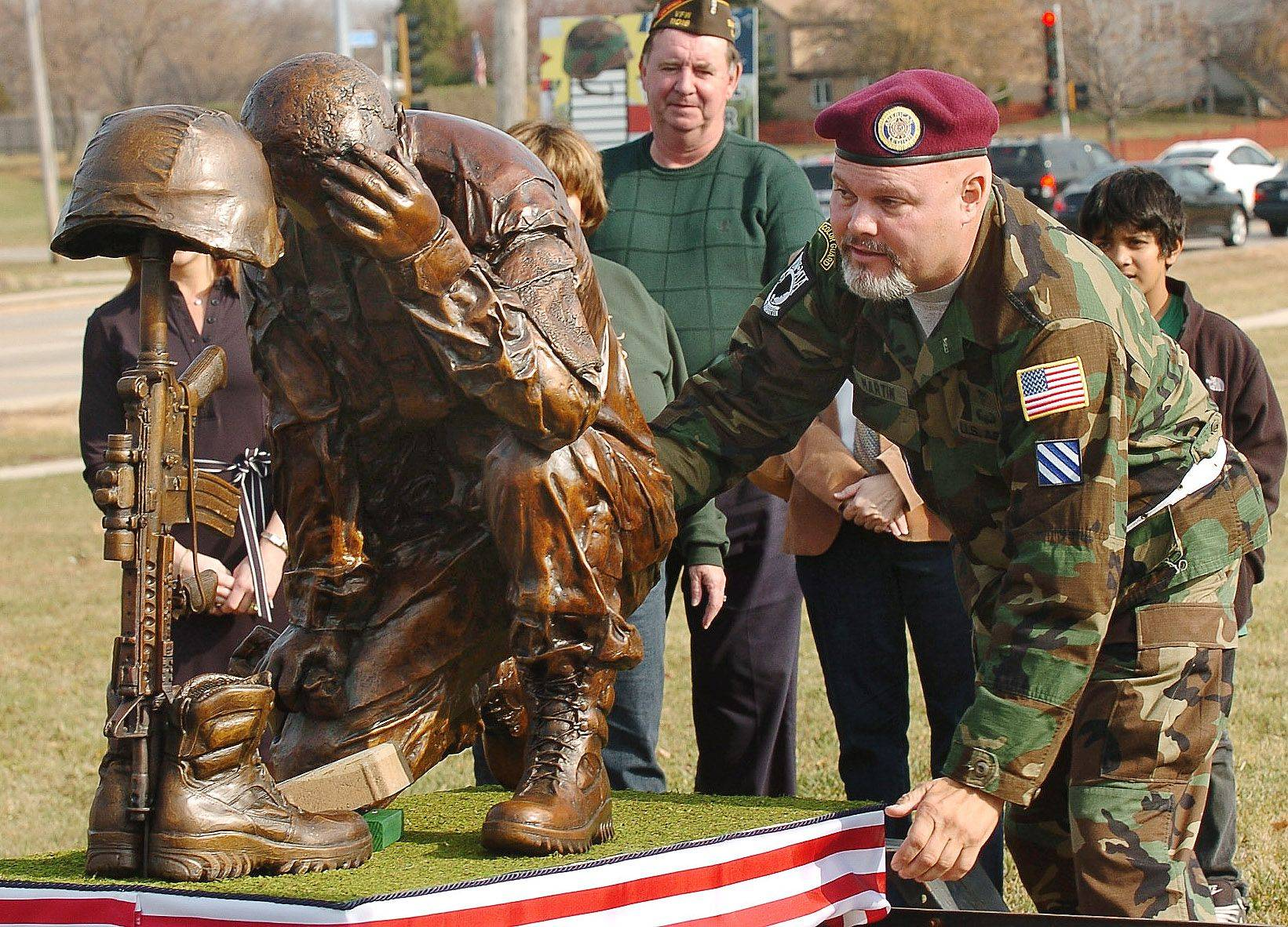 Greg Martin, of American Legion Post 1212 straightens the statue that he designed after unveiling it on the future Veterans Memorial Site in Bartlett during Veterans Day ceremonies.