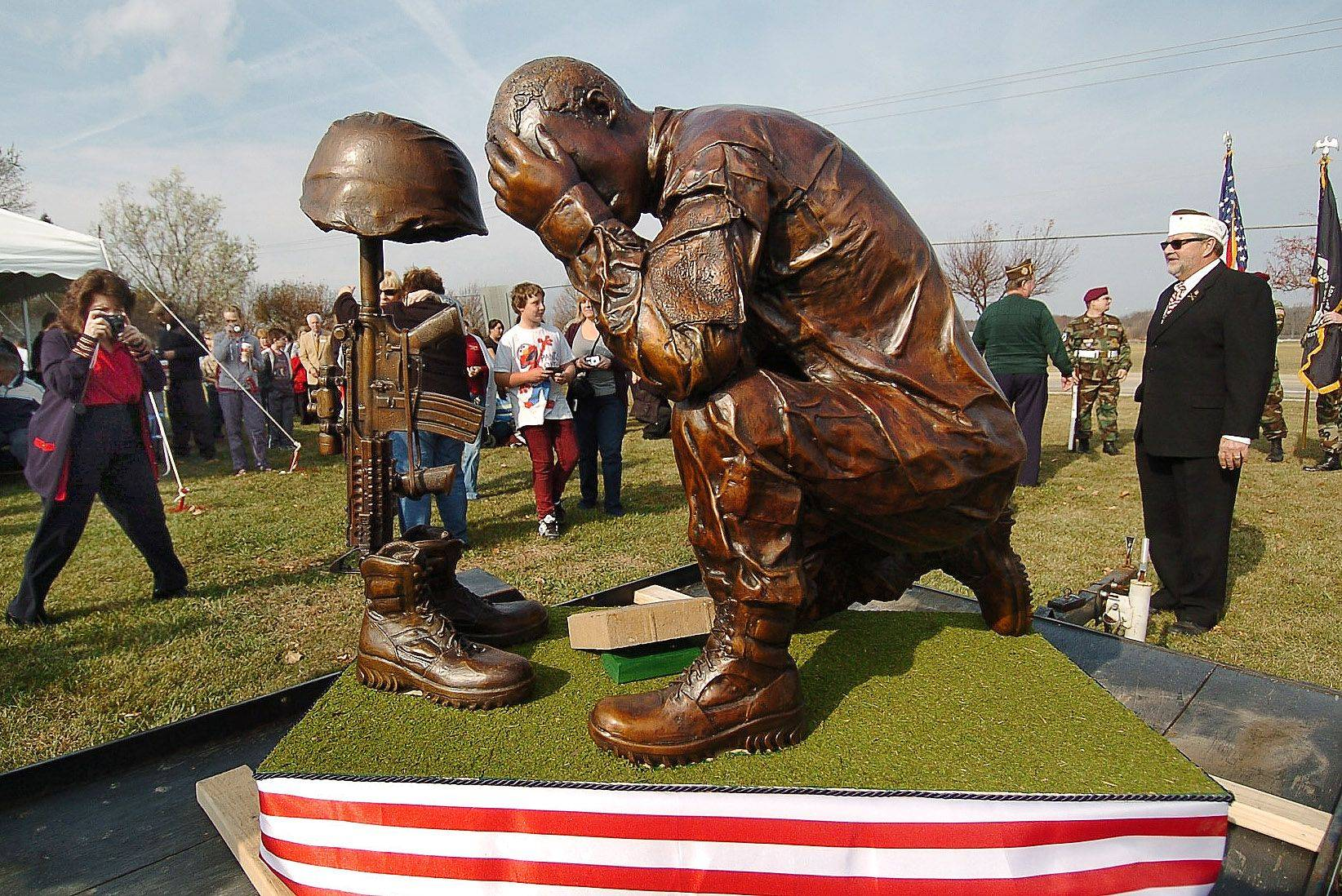 Statue designed by Greg Martin, of American Legion Post 1212, is admired by the gathering during the dedication of the future Veterans Memorial Site in Bartlett during Veterans Day ceremonies.