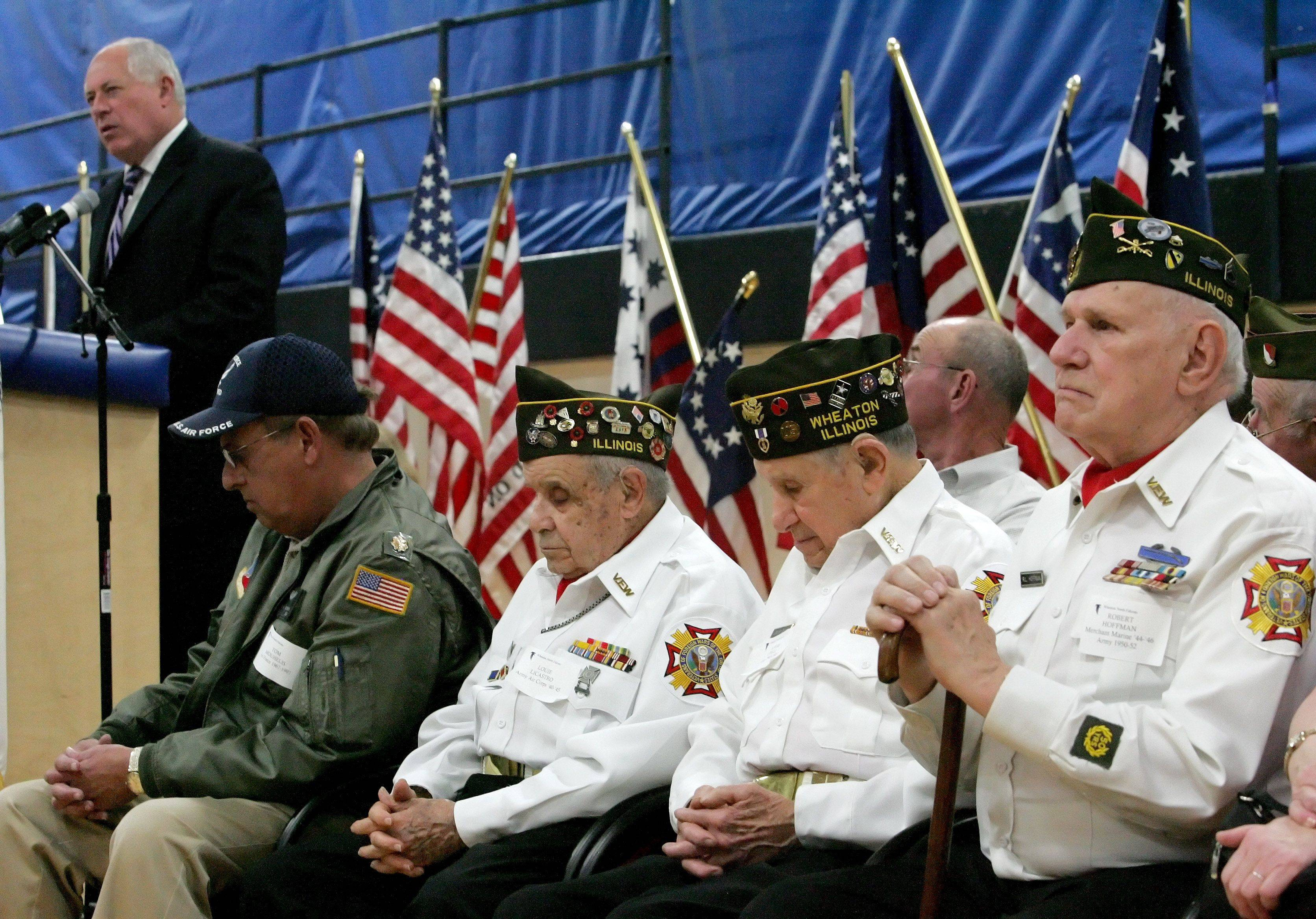 Left to right, veterans Tom Mouhelis, Louie Celli, Louie Licastro and Robert Hoffman listens as Governor Pat Quinn speaks at a Veterans Day event honoring Medal of Honor recipient Staff Sgt. Rob Miller at Wheaton North High School on Thursday.
