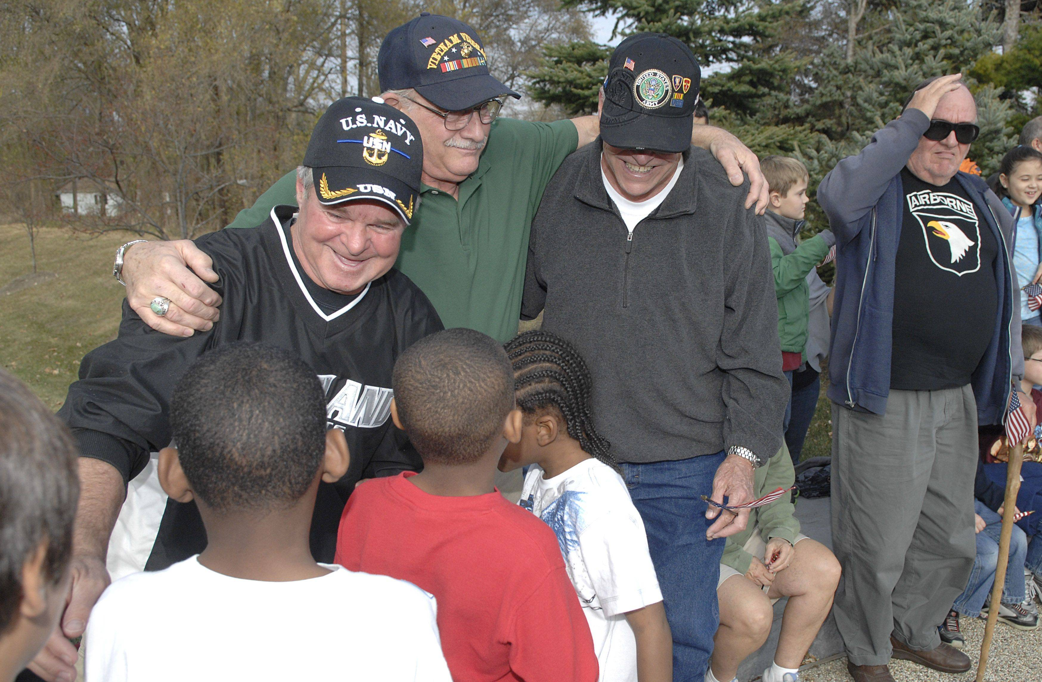 From left, Jim Myers, Jesse Frank, and Phil Jungles, all veterans from North Aurora, receive hugs from Share and Care Learning Center students at the Veterans Day ceremony in North Aurora on Thursday, November 11. Myers, a Navy vet, said it brought tears to his eyes. Frank served in the Marines and Jungles served in the Army.