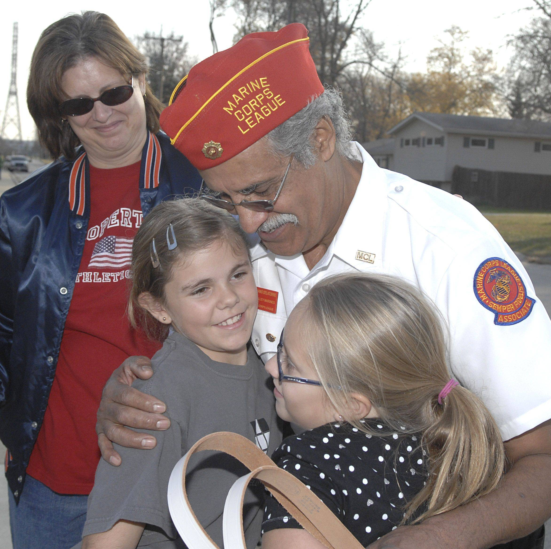 Laura Stoecker/lstoecker@dailyherald.comAureliano Delatorre of Aurora receives a hug from Morgan Lewis, left, and Shelby Balduff, both 10, after the Veterans Day ceremony in North Aurora on Thursday, November 11. Delatorre's son, Jesse, was killed while serving in the Marines in 2007. Morgan and Shelby came from the nearby after school day care Share and Care Learning Center.