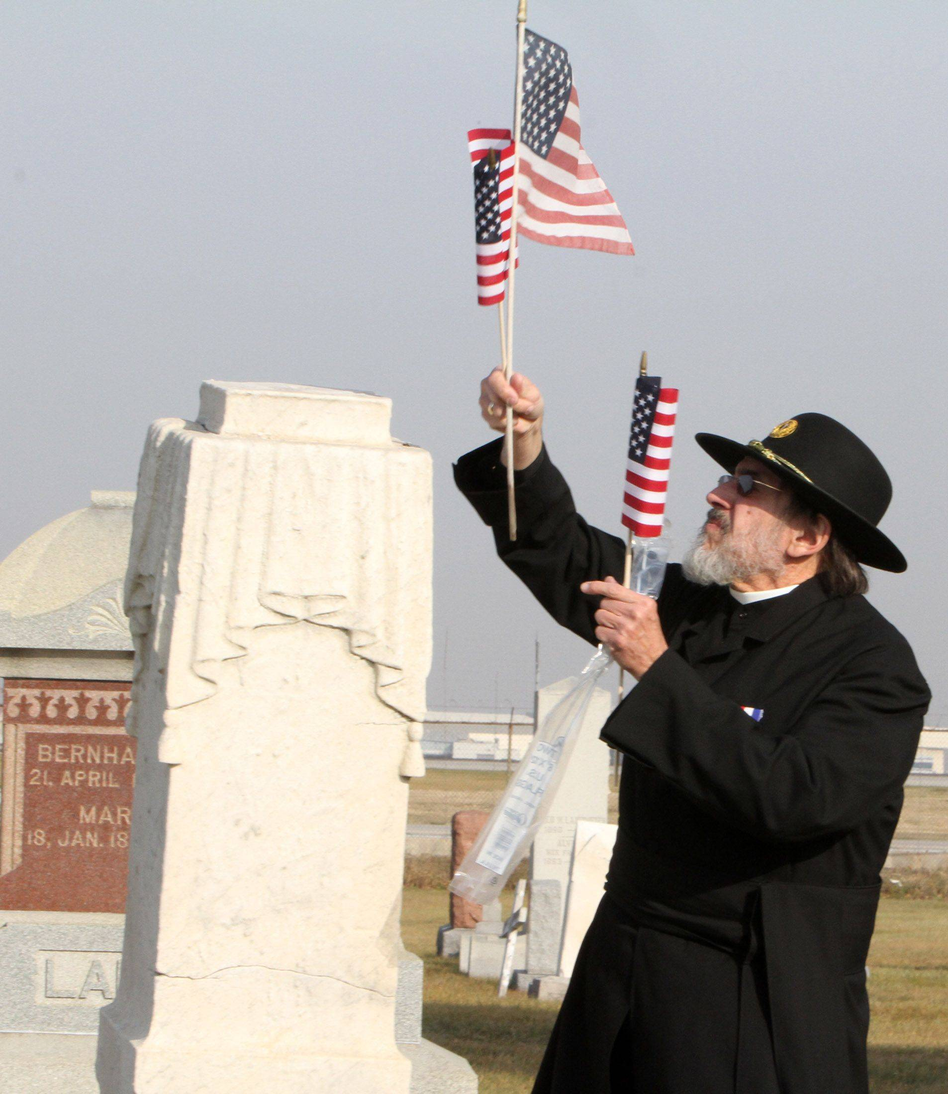Jerry Kowalski, of Elmhurst, National Chaplain for the Sons of Union Veterans of the Civil War places an American Flag at the stone of the Civil War veteran after the memorial ceremony on Veterans Day at Johannes Cemetery just south of O'Hare International Airport in Chicago on Thursday, November 11.