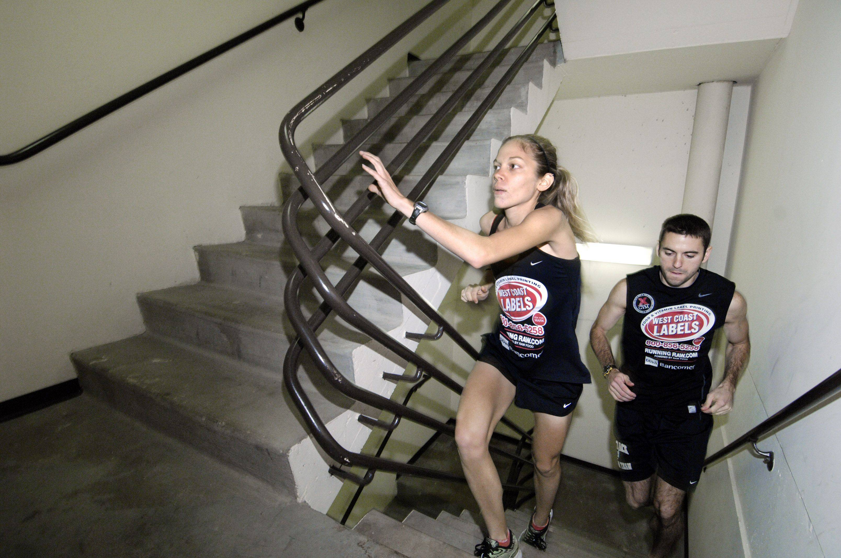 Schaumburg residents and elite stair climbers Kristin Frey, ranked 5th in world, and Braden Renshaw, ranked 29th in the world, train in the stairwell of a Schaumburg building in preparation for the stair climbing competition at Willis Tower Sunday. Renshaw climbs barefoot.