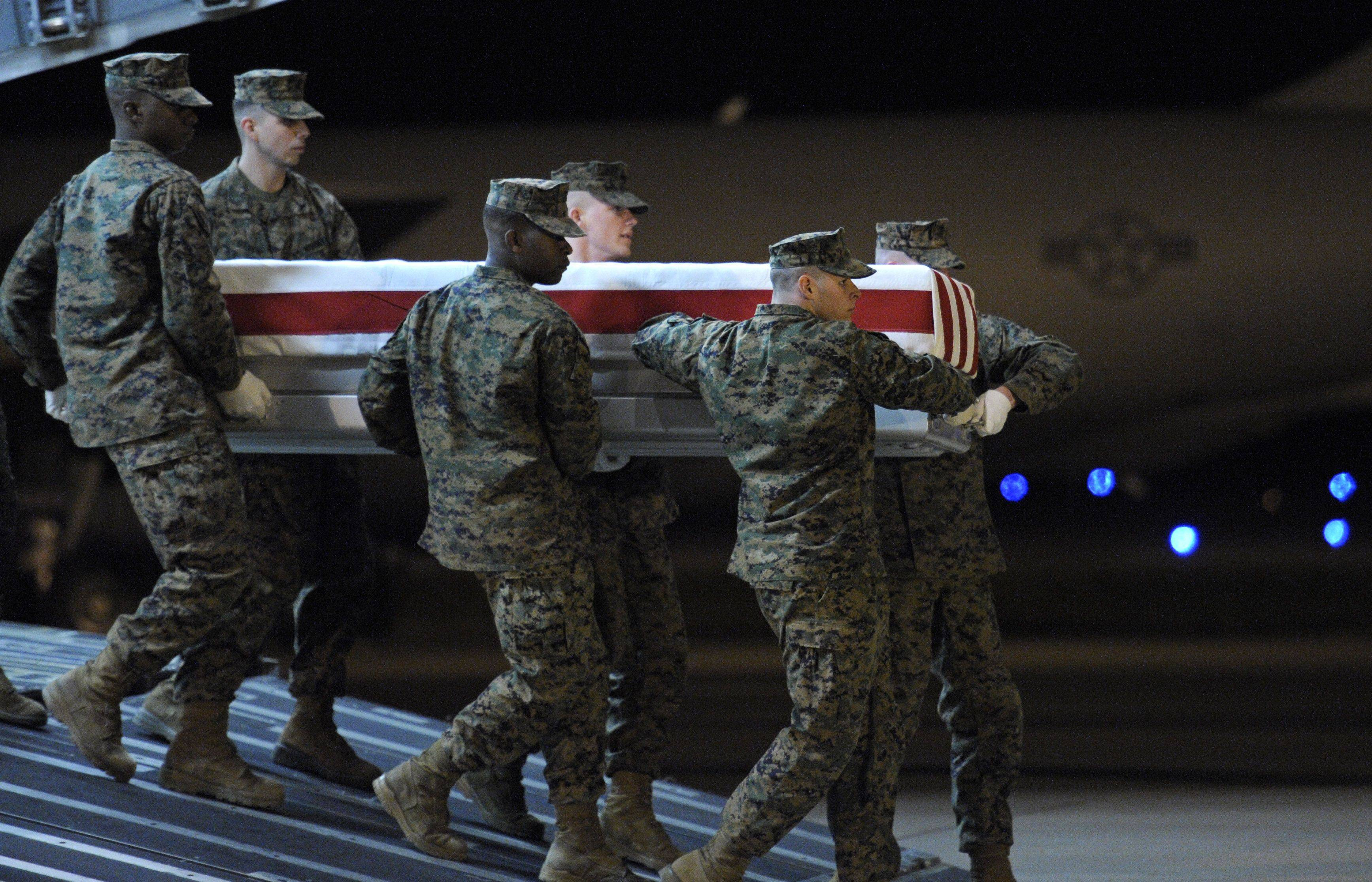 A Marine Corps team carries the flag-draped casket of Marine Lance Cpl. James Stack, 20, of Arlington Heights at Dover Air Force Base in Delaware Friday.