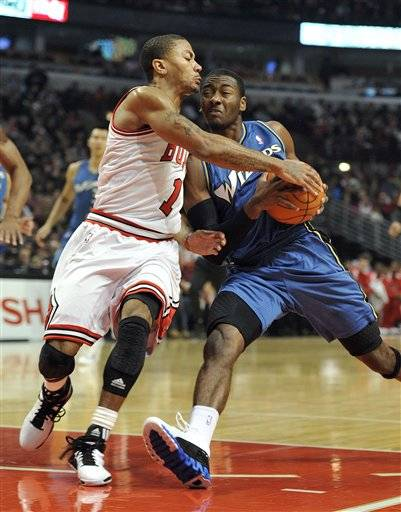 s Derrick Rose knocks the ball away from the Washington Wizards' John Wall during the first half .