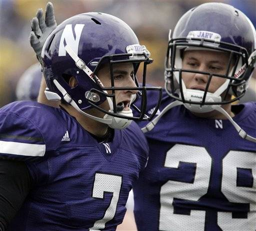 Northwestern quarterback Dan Persa, left, celebrates with Mike Trumpy after Persa scoring on a short touchdown run during the first quarter.