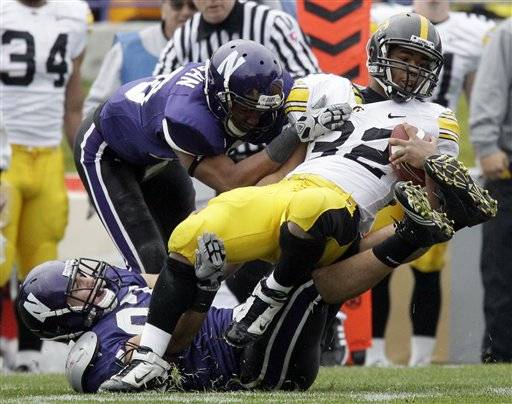 Iowa running back Adam Robinson is tackled by Northwestern's Justan Hanrahan and Tyler Scott during the first quarter .