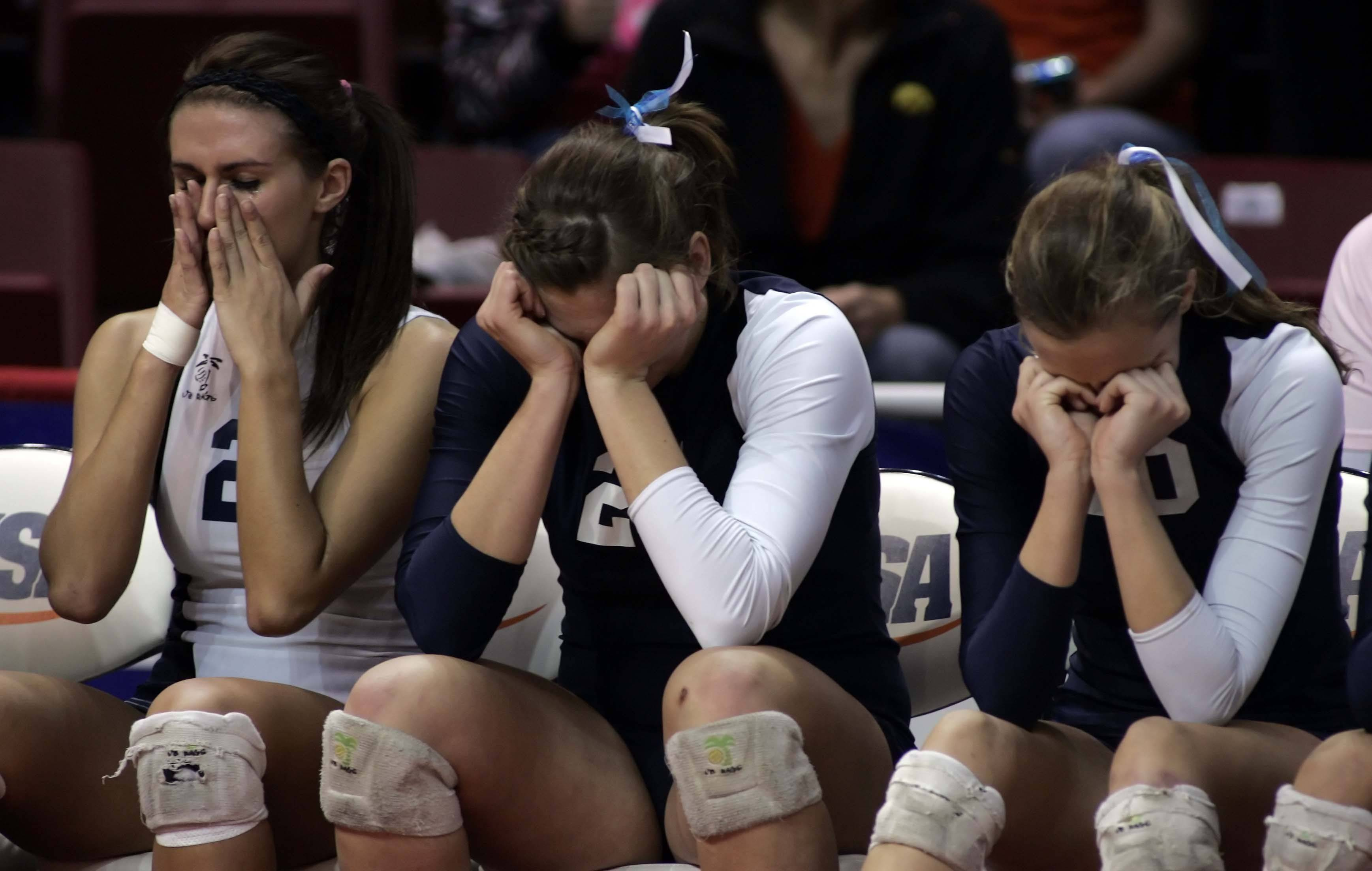 Cary-Grove libero Sam Mainzer, 2, from left, middle blocker Ashley Rosch, 25, and outside hitter Melanie Jereb, 10, react after losing to Lyons in the IHSA Class 4A State championship match Saturday, November 13, 2010 at Redbird Arena in Normal.