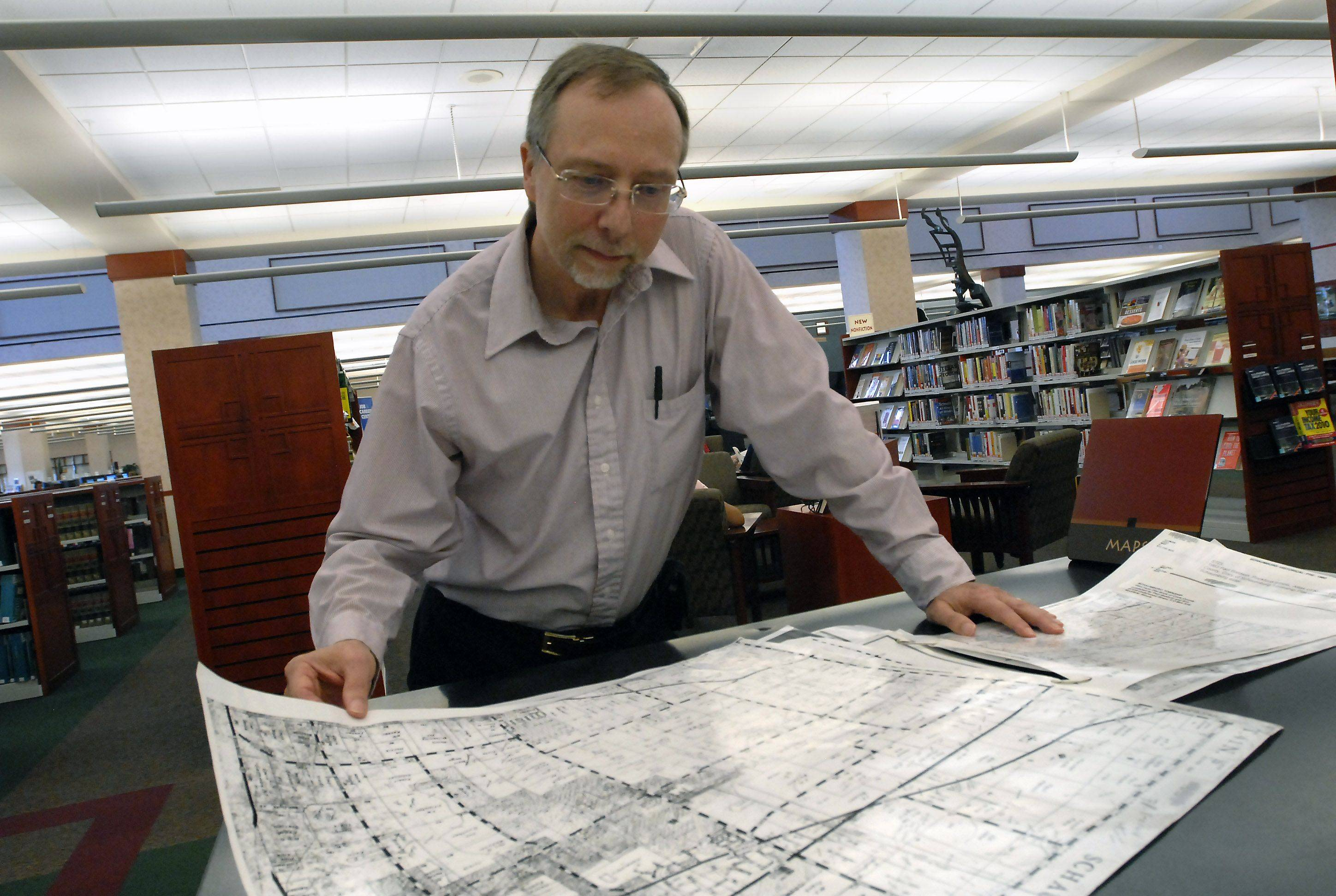 Schaumburg Township Library genealogy coordinator Tony Kierna looks over some county maps at the library.