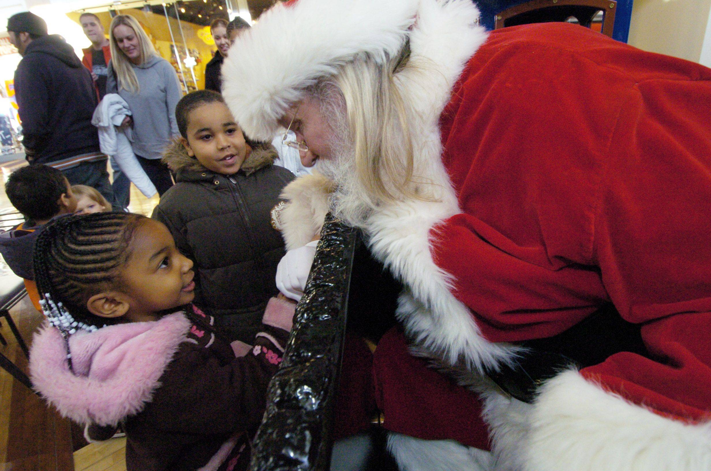 Santa Claus greets Lillie Nelson, 4, of Waukegan and her brother, Damarion Cole, 6, at Gurnee Mills Saturday.
