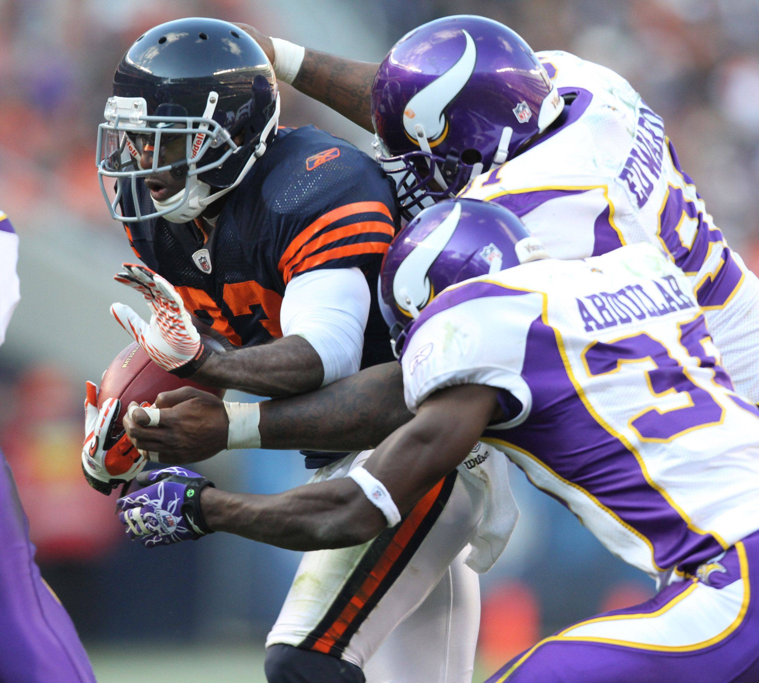 Chicago Bears's Devin Hester is pulled down during a punt return by Minnesota Vikings' Husain Abodullah and Ray Edwards in the second half.