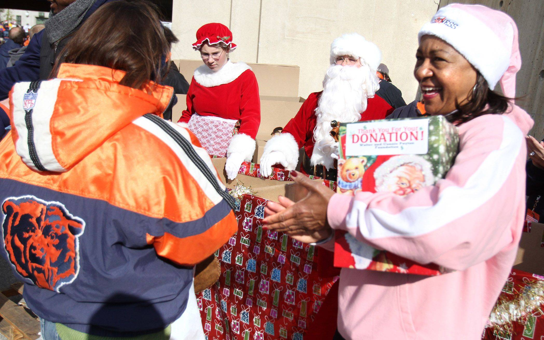 Connie Payton collects toys with Santa Claus and Ms. Claus for The Walter and Connie Payton Foundations before the Chicago Bears against Minnesota Vikings at Soldier Field.