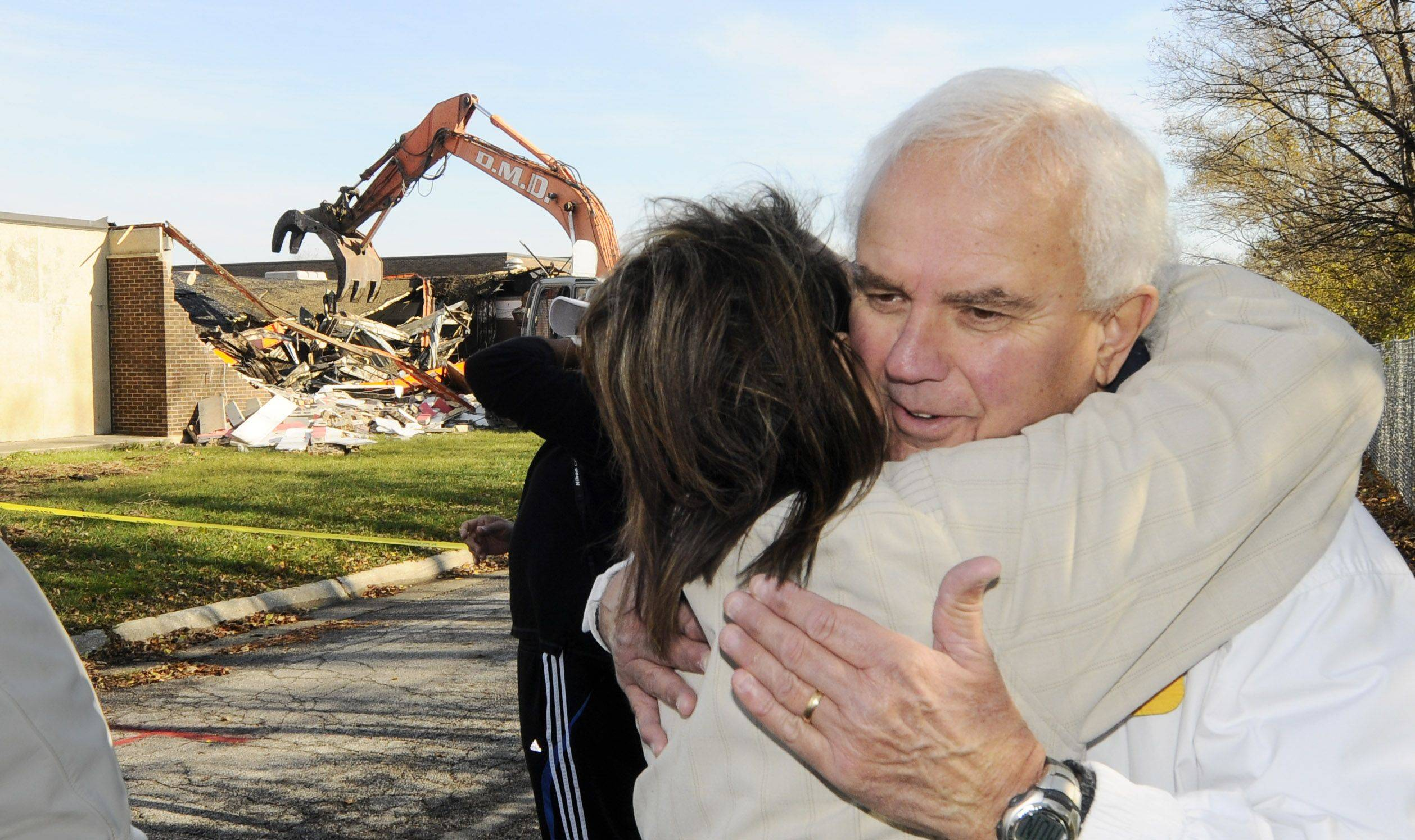 Former Driscoll student Veronica Togtman hugs family friend Dave Faydash as demolition work began Monday morning at the former Driscoll Catholic High School in Addison. In about two weeks, Driscoll supporters can pick up bricks from the building at Addison Public Works.