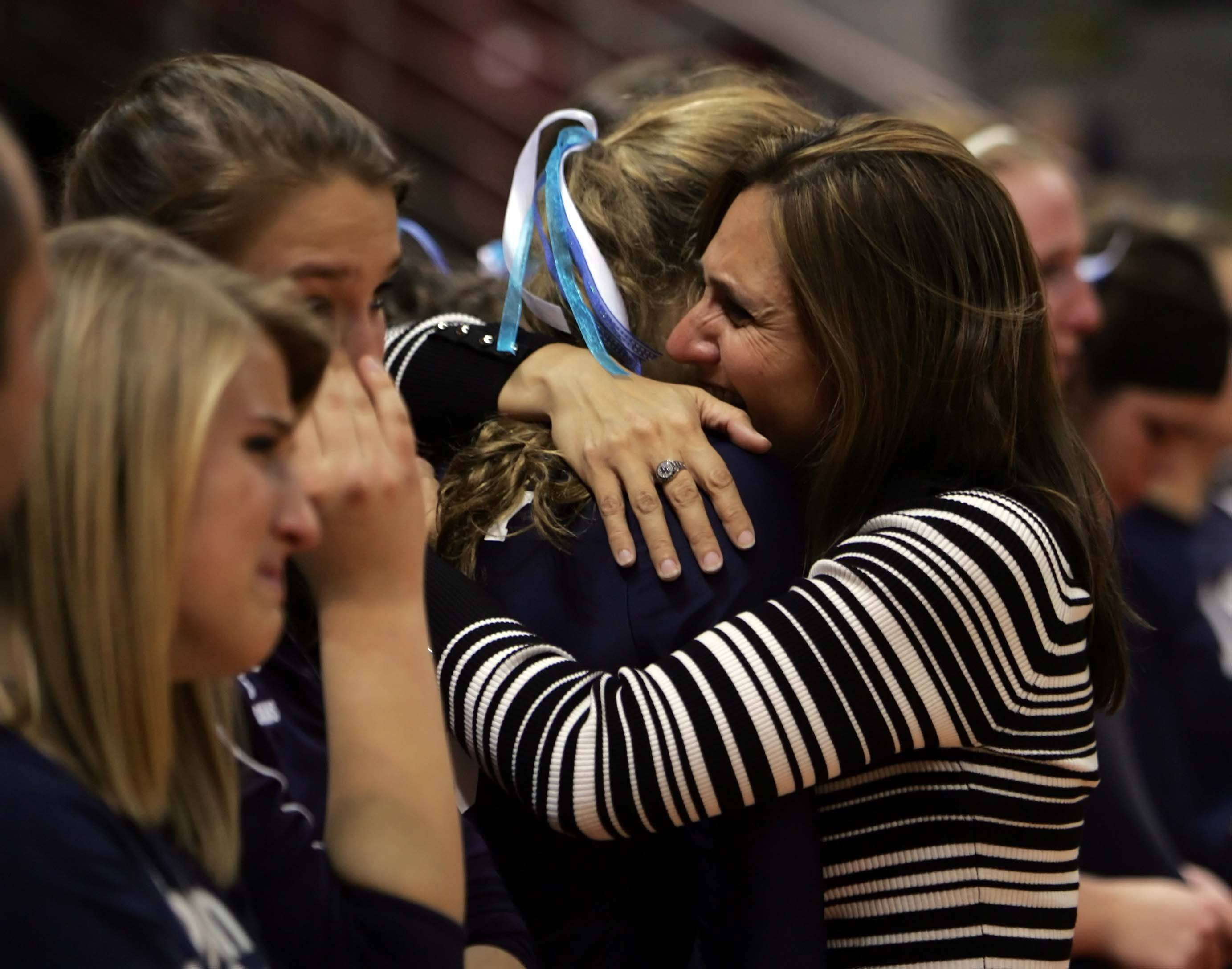Cary-Grove coach Patty Langanis hugs her players after their loss to Lyons in the IHSA Class 4A State championship match Saturday.