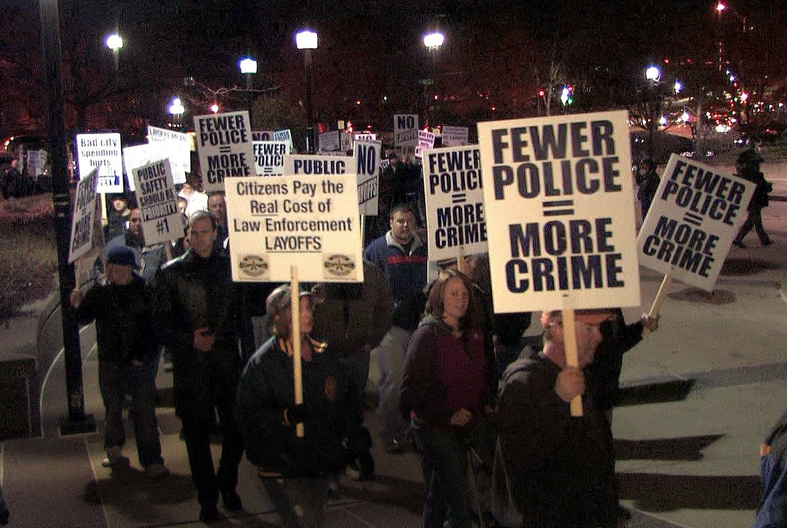 Naperville police union members and their supporters conduct an informational picket on Tuesday outside city hall to protest the layoffs of six police officers.