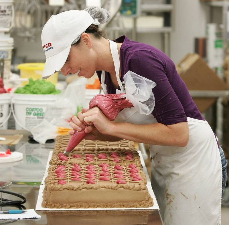 bakery manager janet behrick decorates chocolate cakes in preparation for the saturday opening of costco in