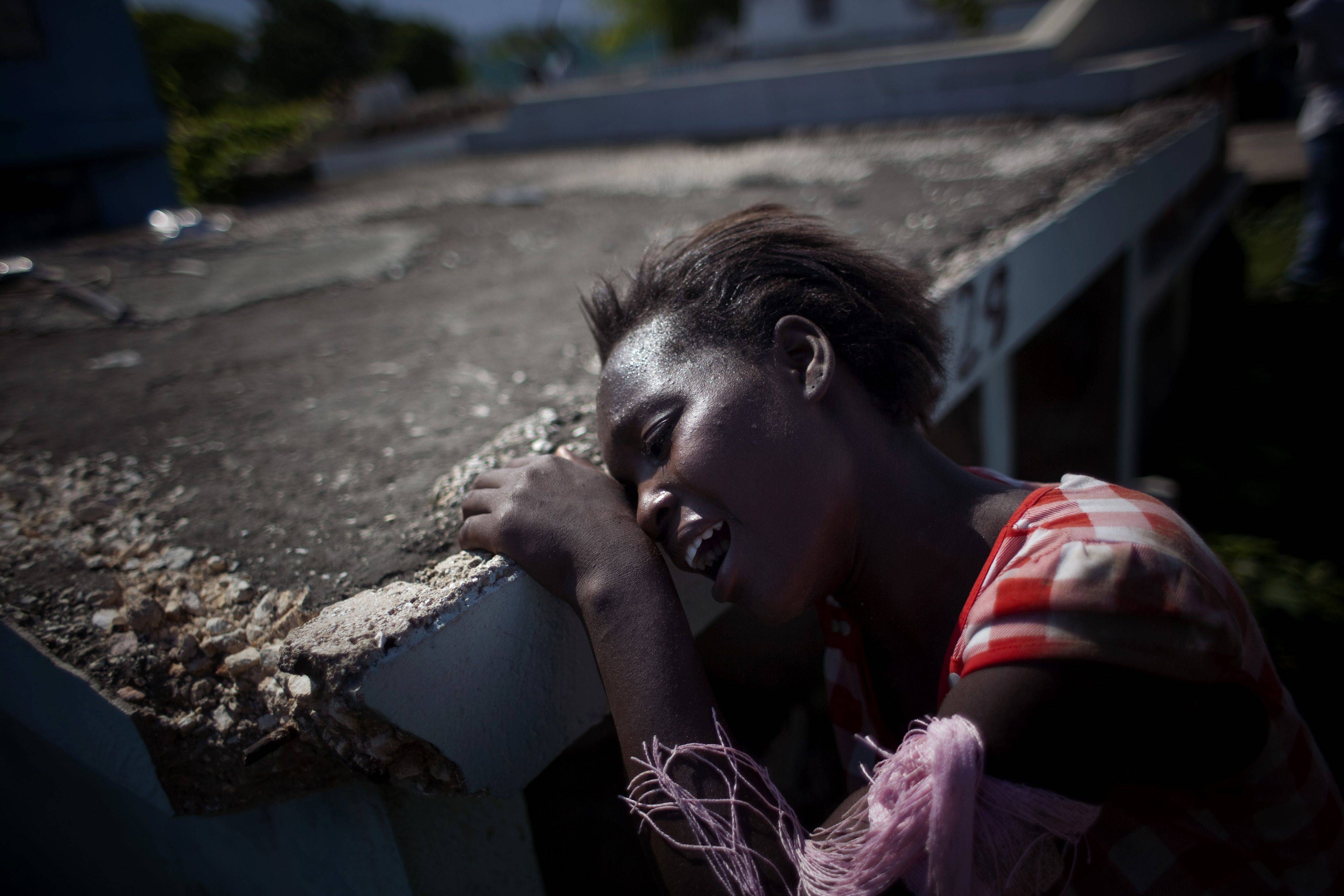 A relative of Monitha Silney, 12, who died of cholera, mourns during her burial at the cemetery Sunday in the slum of Cite Soleil in Port-au-Prince, Haiti. Thousands of people have been hospitalized for cholera across Haiti with symptoms including serious diarrhea, vomiting and fever and hundreds have died.