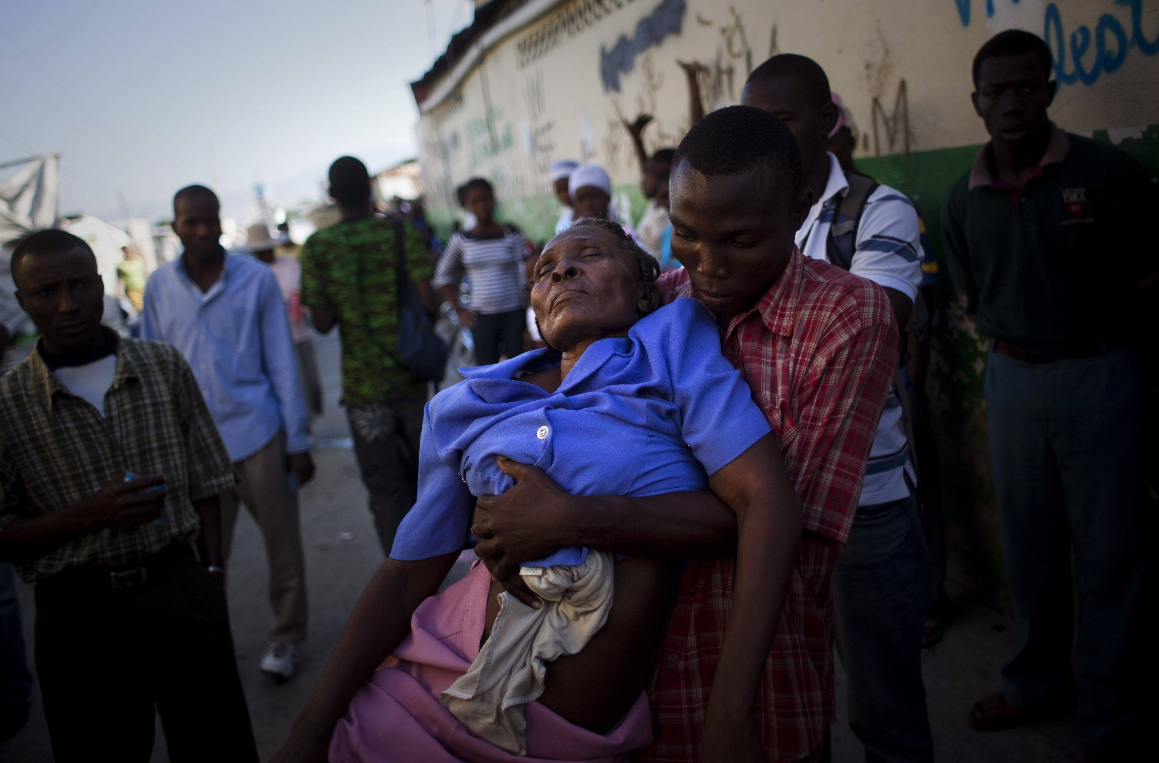 A woman suffering cholera symptoms is carried to St. Catherine hospital, run by Doctors Without Borders, in the Cite Soleil slum in Port-au-Prince, Haiti, on Monday