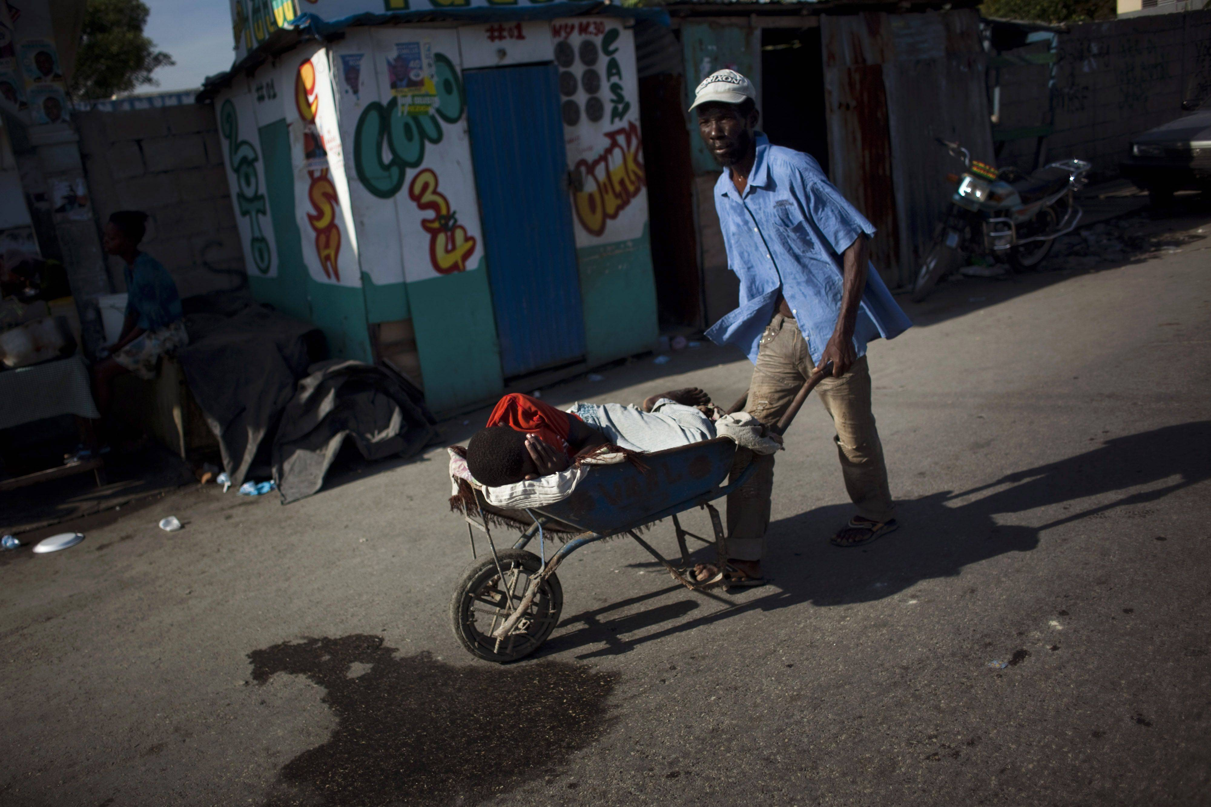 A man pushes a boy suffering cholera symptoms in a wheelbarrow to St. Catherine hospital, run by Doctors Without Borders, in the Cite Soleil slum in Port-au-Prince, Haiti. Thousands of people have been hospitalized for cholera across Haiti with symptoms including serious diarrhea, vomiting and fever and hundreds have died.