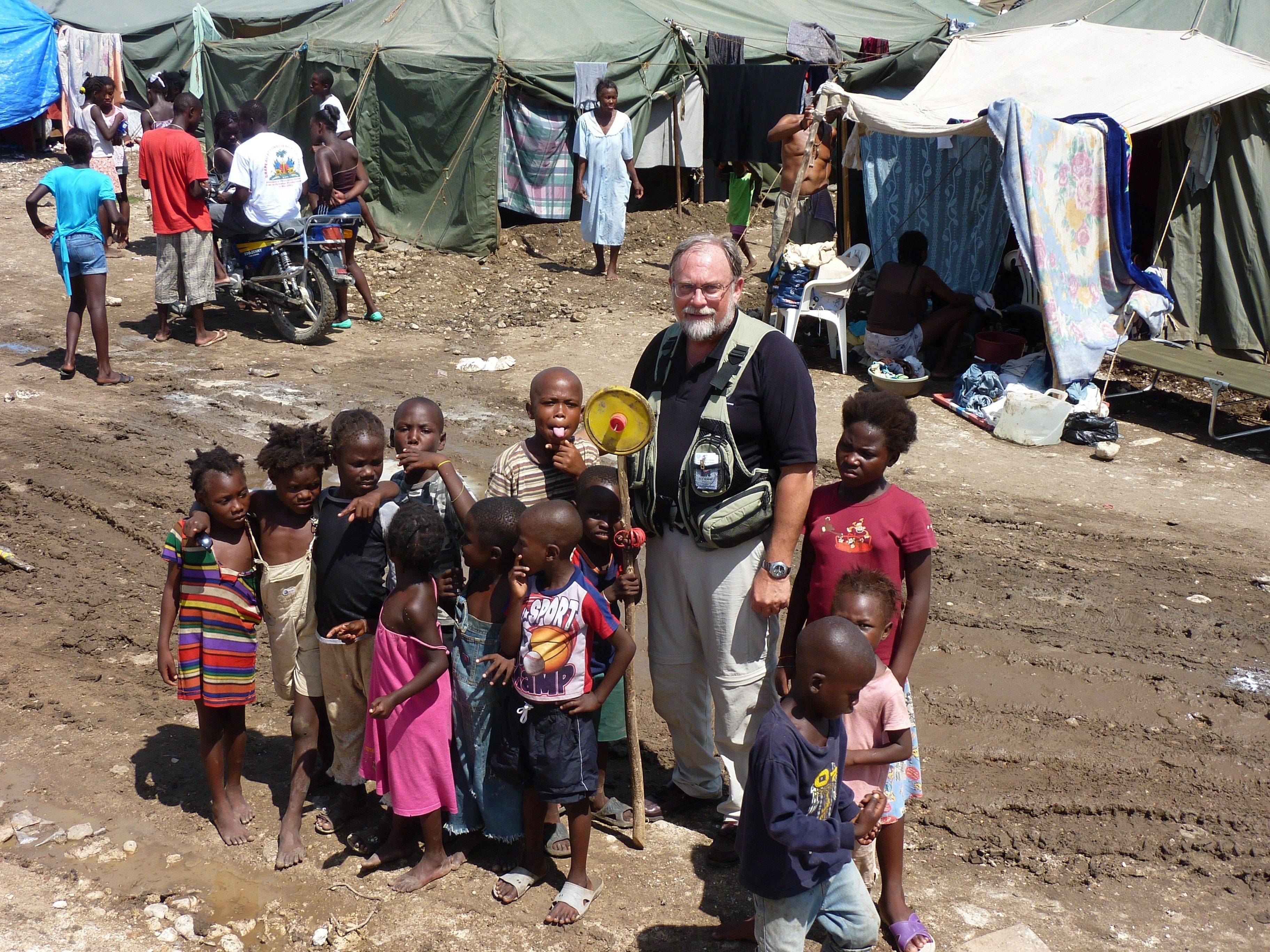 Tim Hetzner, of Palatine, president of Lutheran Church Charities in Addison, poses with some of the children he met during a trip to Haiti this summer.