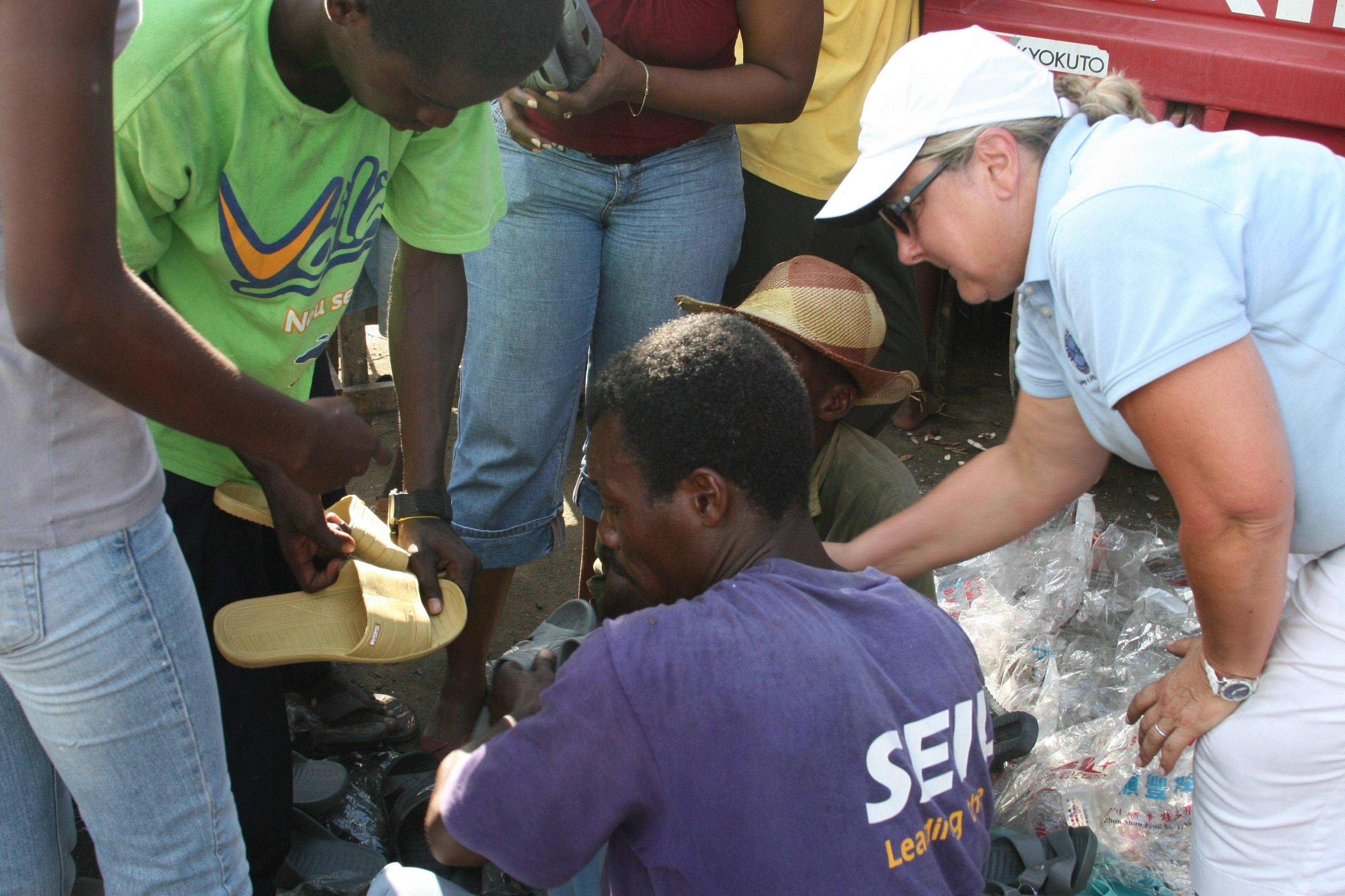 Dona Martin, of Barrington, hands out plastic shoes to Haitians during a recent trip there with Addison-based Lutheran Church Charities.
