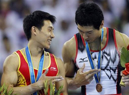 Gold medalist China's Teng Haibin, left, explains to bronze medalist Japan's Hisashi Mizutori the hand gesture he made during the medal ceremony.