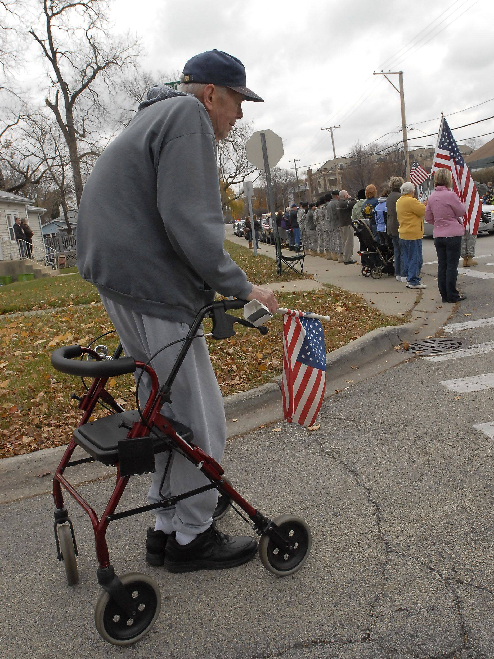 Korean War veteran Roger Steingraber of Arlington Heights bows his head Thursday as the body of Marine James Bray Stack passes by on Miner Street in Arlington Heights.