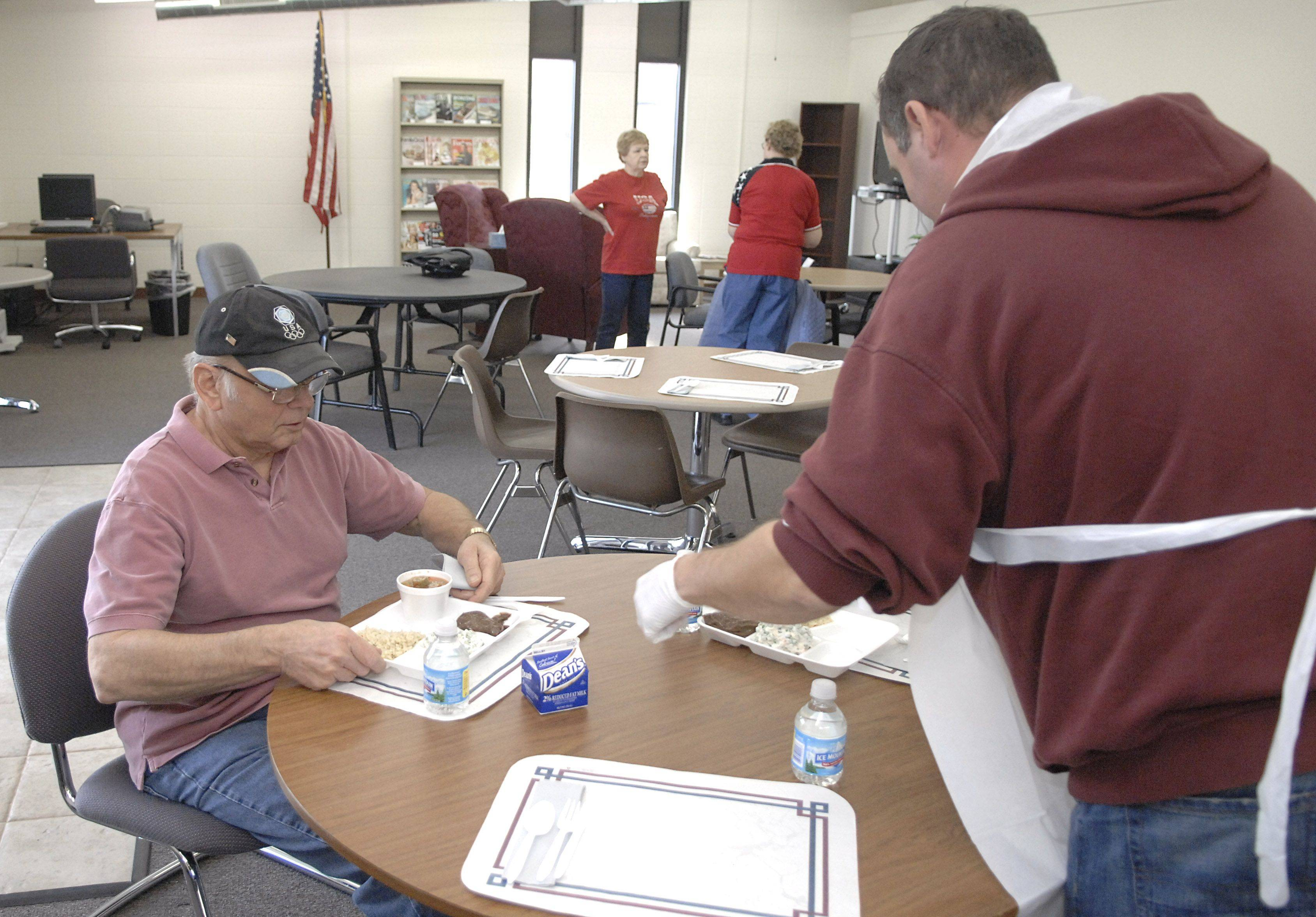 Chris Walker, Sugar Grove Older Adult Center's director, serves a hot lunch to Dan Palmer of North Aurora on Veterans Day. After lunch, seniors often gather to play card games.