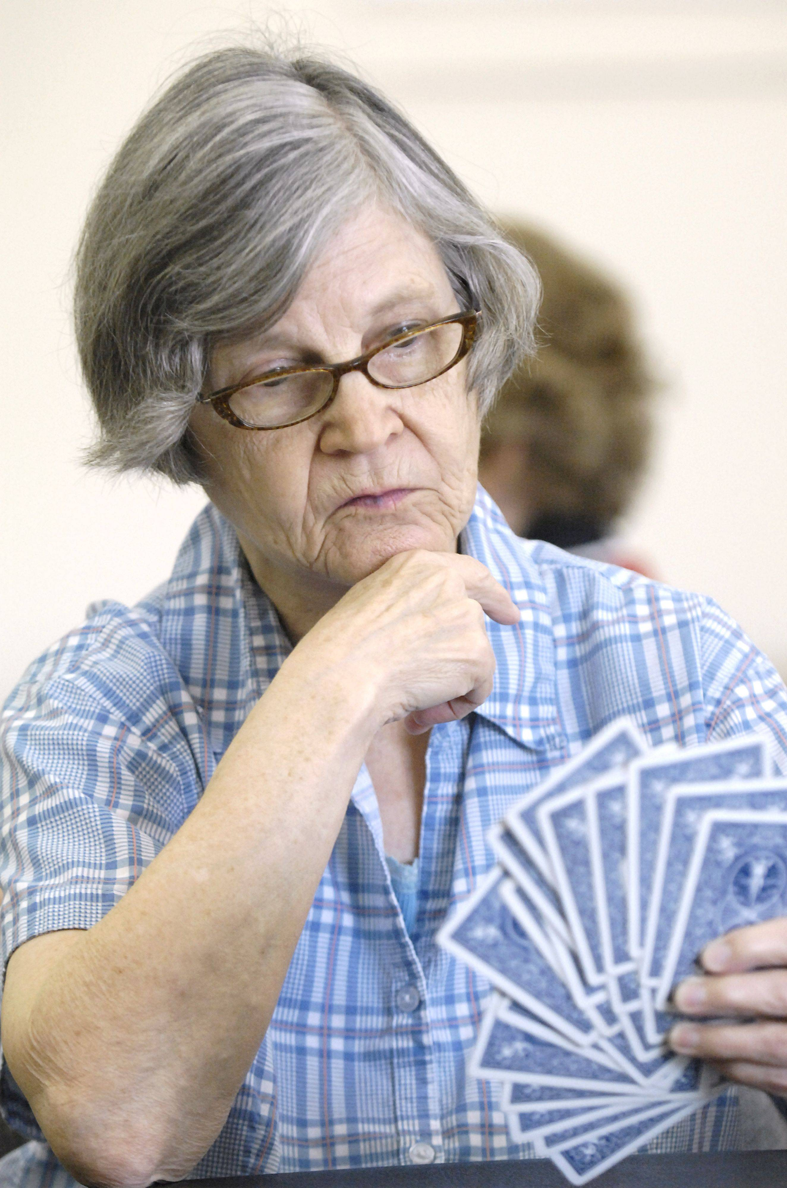 Ruth Weekly of Sugar Grove ponders her next move in a game of pinochle at the Sugar Grove Older Adult Center.