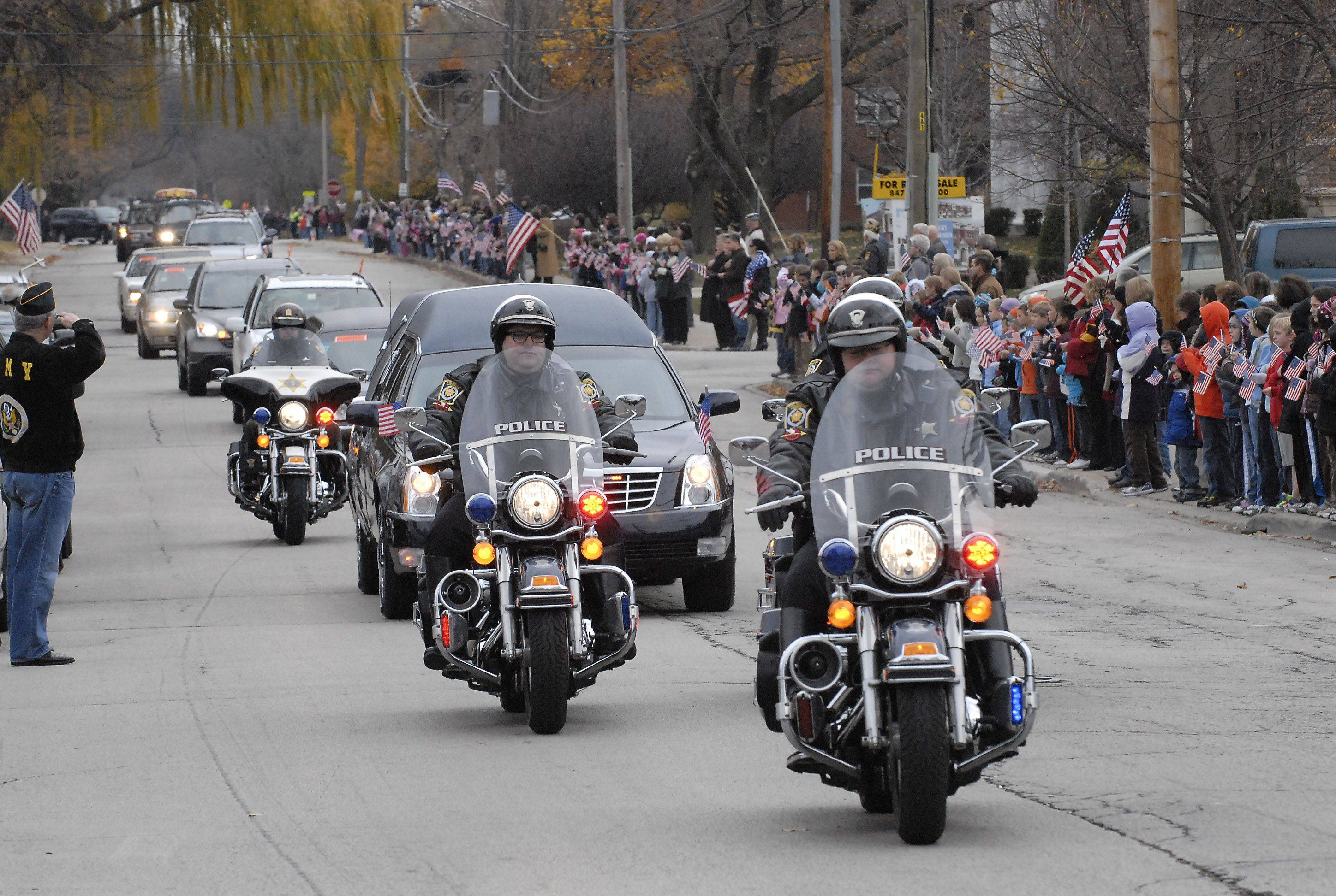 The motorcade for Marine James Bray Stack passes by American Legion Post 208 on Miner Street Thursday in Arlington Heights, where about 500 veterans and students from Windsor Elementary School lined the street.