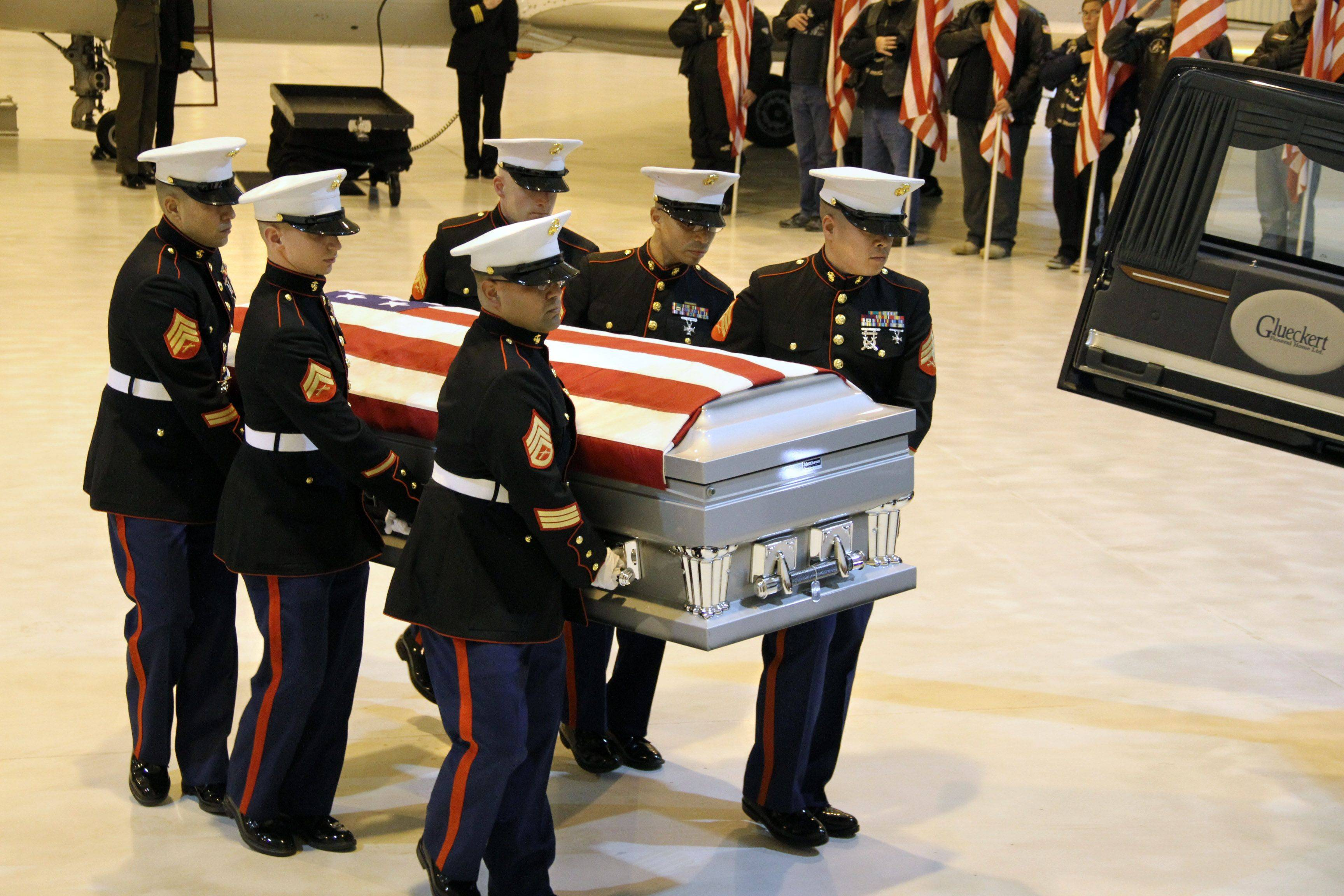 A Marine Corps team carries the flag-draped casket of Marine Lance Cpl. James Stack, 20, of Arlington Heights at Chicago Executive Airport in Wheeling .