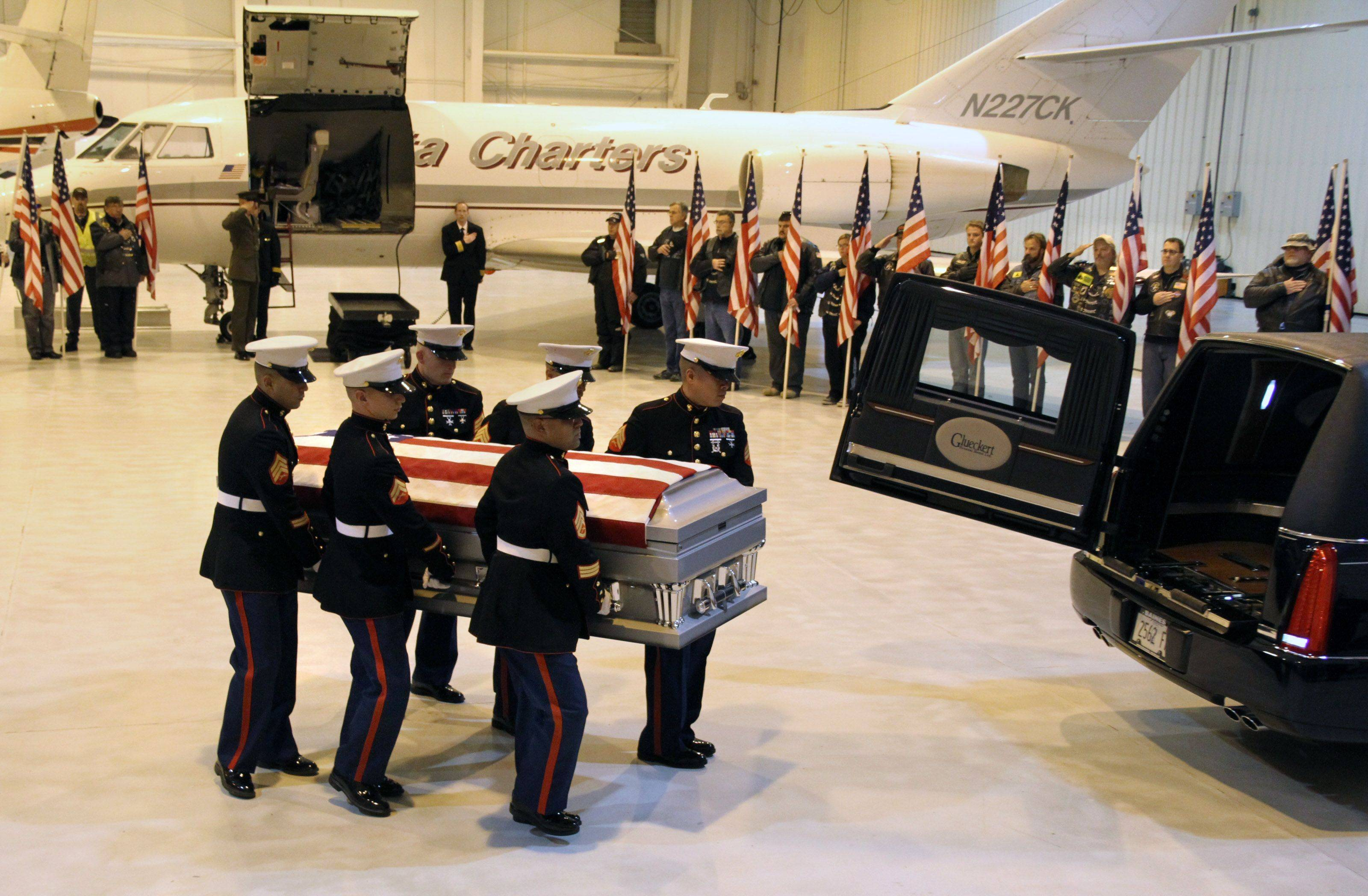 George LeClaire/gleclaire@dailyherald.comA Marine Corps team carries the flag-draped casket of Marine Lance Cpl. James Stack, 20, of Arlington Heights at Chicago Executive Airport in Wheeling