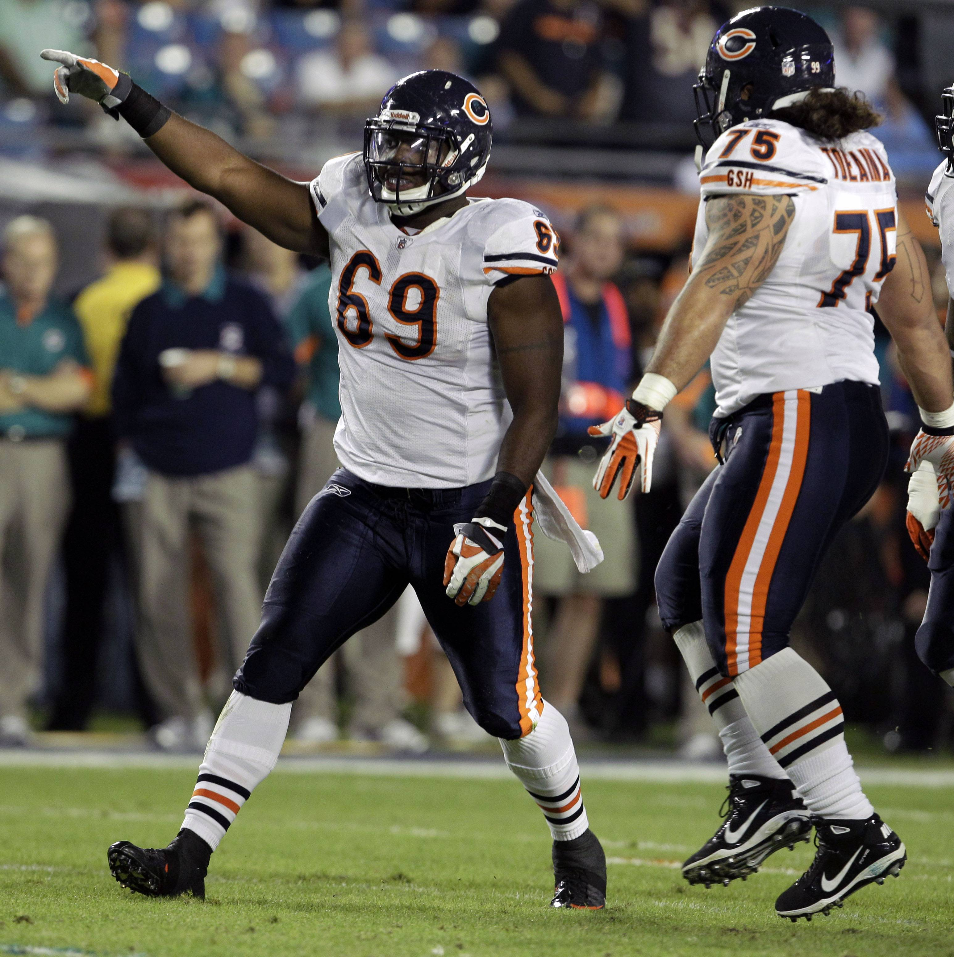 Bears defensive end Henry Melton celebrates with defensive tackle Matt Toeaina after sacking Miami Dolphins quarterback Tyler Thigpen.