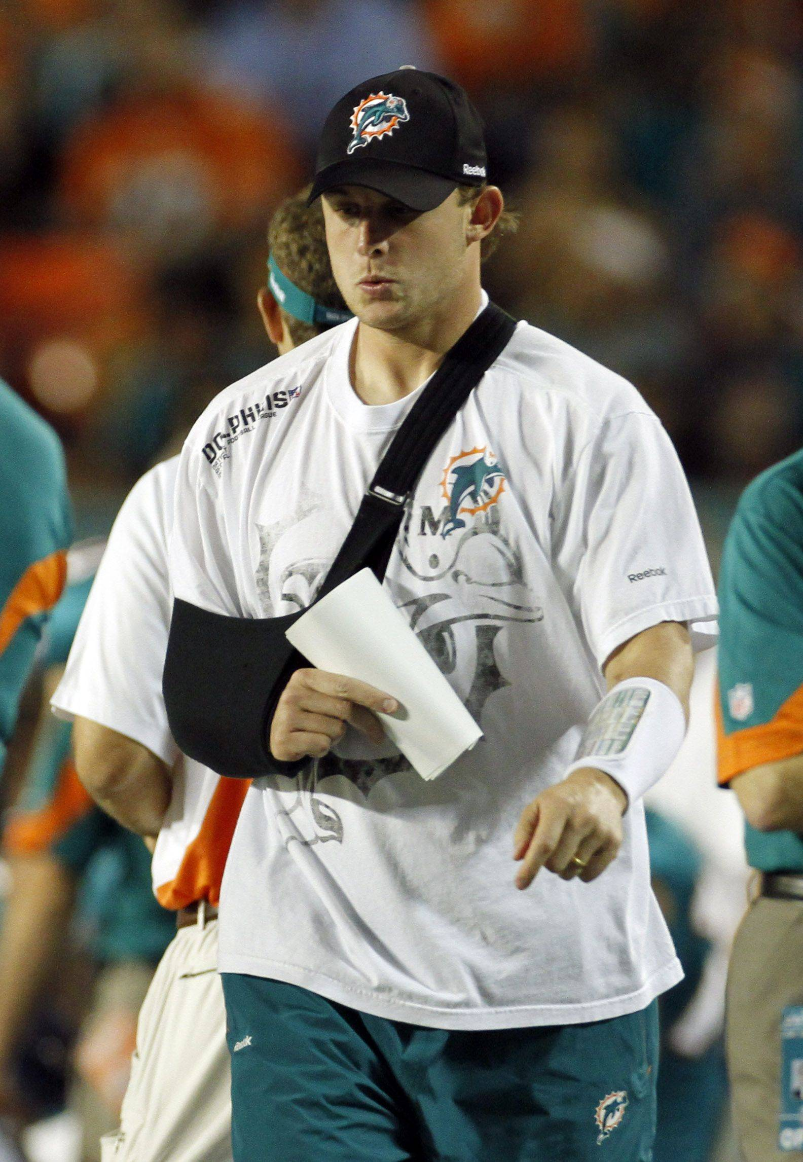 Miami Dolphins quarterback Chad Pennington walks the sidelines with his right arm in a sling.