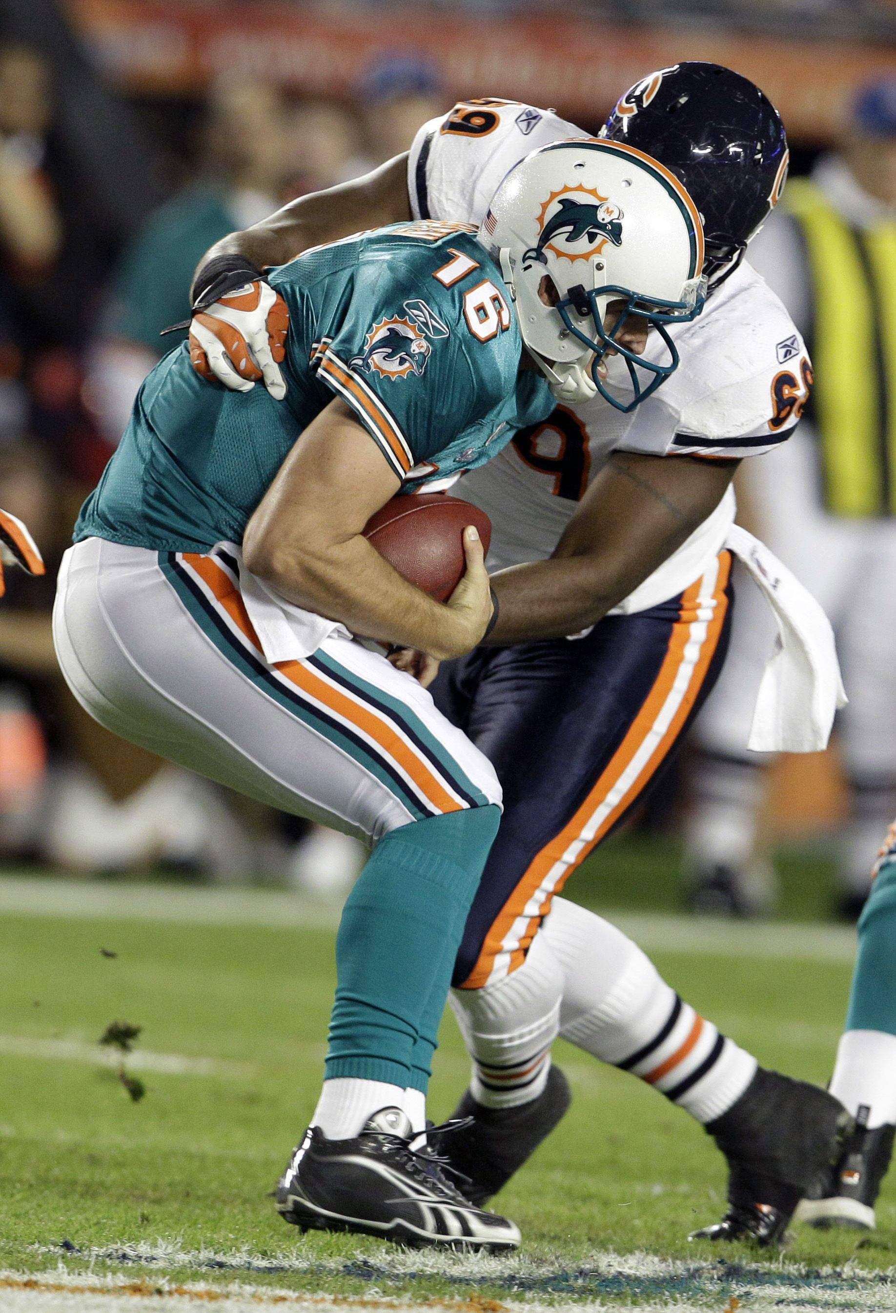 Chicago Bears defensive end Henry Melton sacks Miami Dolphins quarterback Tyler Thigpen during the first quarter .